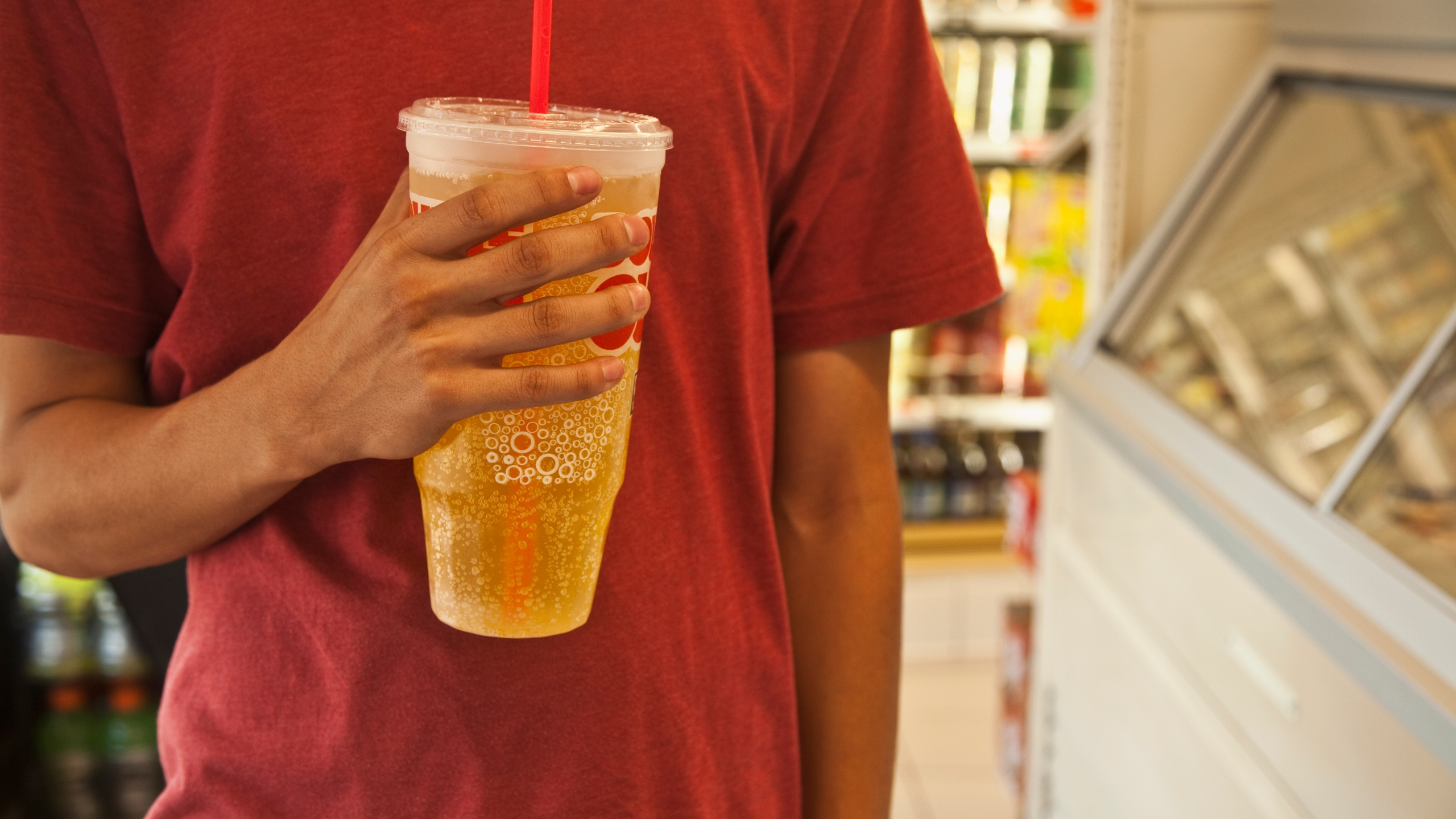 A man holds a giant cup of soda at a convenience store. (Credit: Sarah Fix via Getty Images)