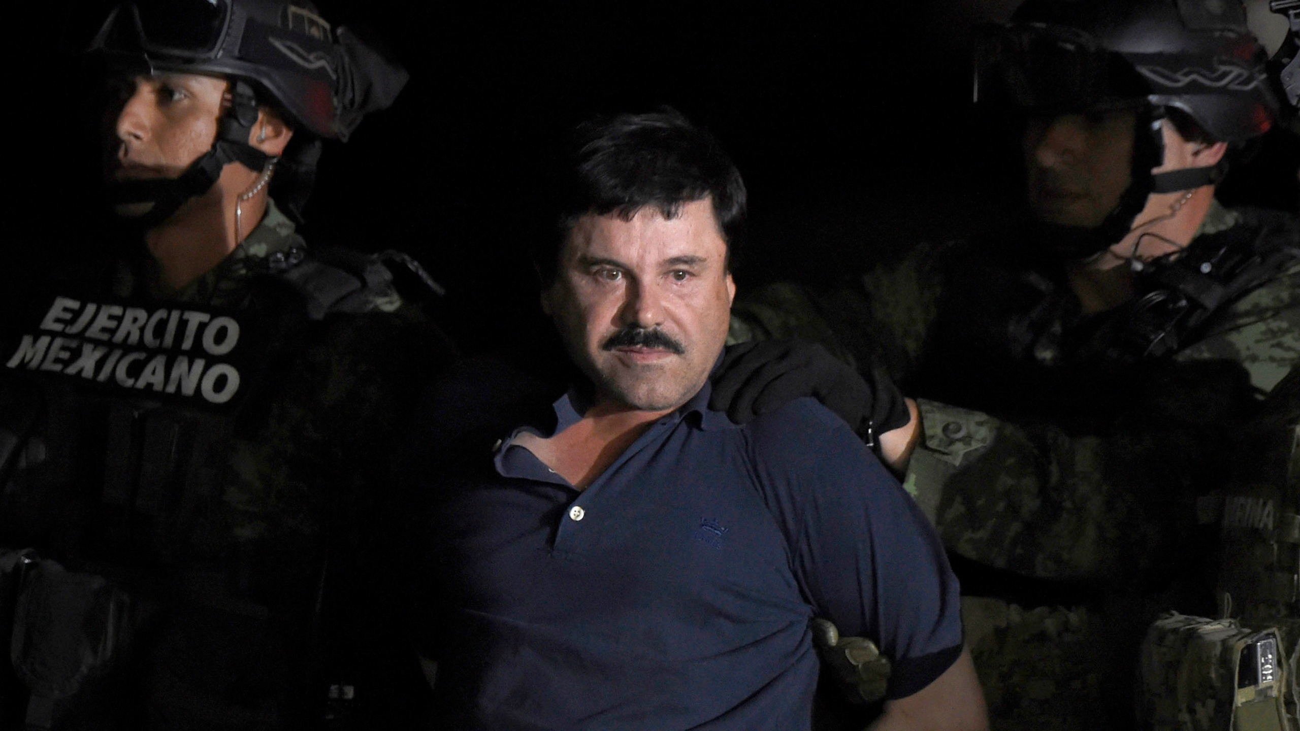"""Joaquin """"El Chapo"""" Guzman is escorted into a helicopter at Mexico City's airport on Jan. 8, 2016 following his recapture during an intense military operation in Los Mochis, in Sinaloa State. (Credit: ALFREDO ESTRELLA/AFP/Getty Images)"""