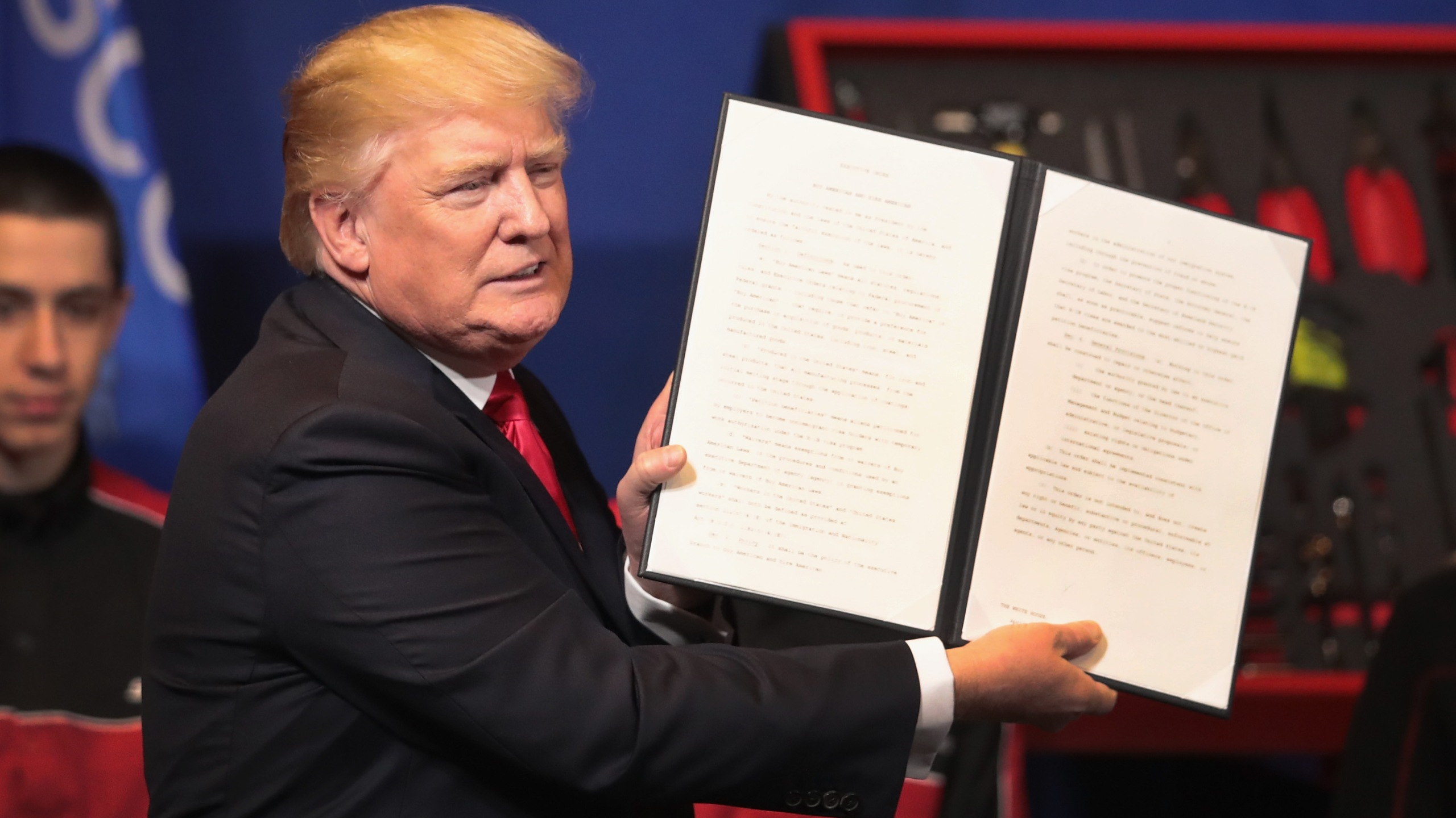 Donald Trump signs an executive order to try to bring jobs back to American workers and revamp the H-1B visa guest worker program during a visit to the headquarters of tool manufacturer Snap-On on April 18, 2017 in Kenosha, Wisconsin. (Credit: Scott Olson/Getty Images)