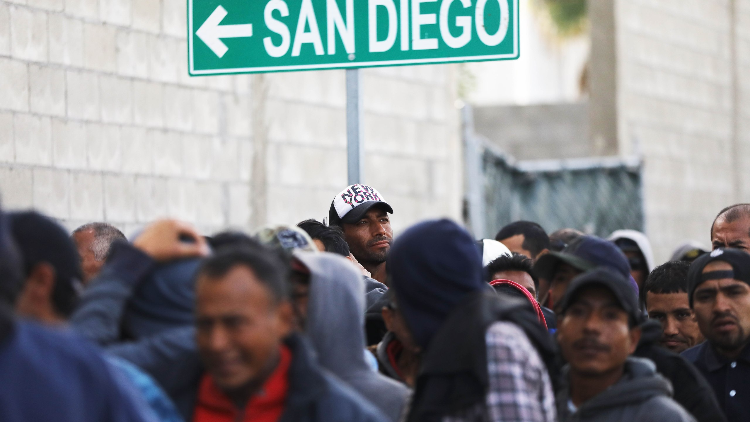 Migrants line up for free breakfast at the Desayunador Salesiano Padre Chava shelter and soup kitchen in front of sign for San Diego on March 9, 2018 in Tijuana, Mexico. (Credit: Mario Tama/Getty Images)