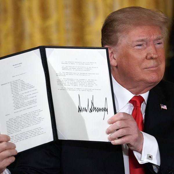 Donald Trump holds up an executive order that he signed during a meeting of the National Space Council at the East Room of the White House June 18, 2018 in Washington, D.C. (Credit: Alex Wong/Getty Images)