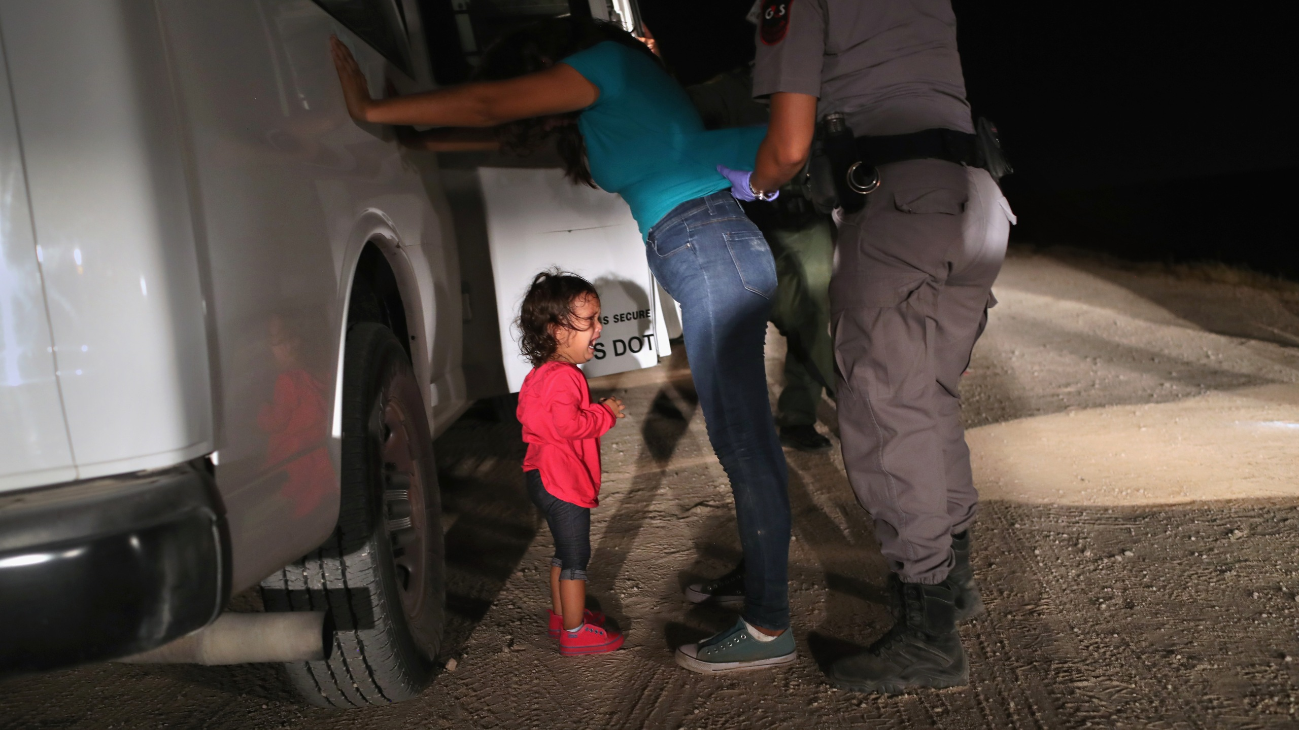A two-year-old Honduran asylum seeker cries as her mother is searched and detained near the U.S.-Mexico border on June 12, 2018, in McAllen, Texas. (Credit: John Moore/Getty Images)