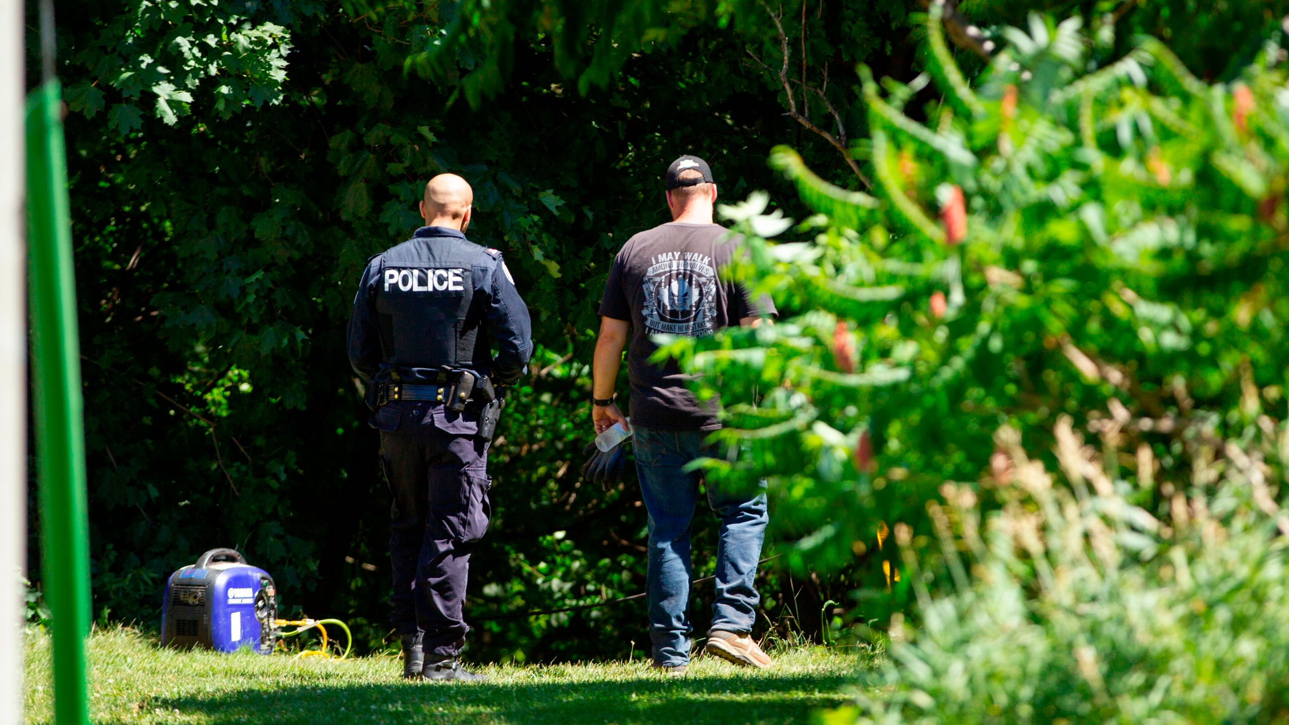 Investigators walk near a ravine behind a home on Mallory Crescent in Toronto, Ontario, July 6, 2018 where human remains were discovered in connection to the case of serial killer Bruce McArthur. (Credit: GEOFF ROBINS/AFP/Getty Images)