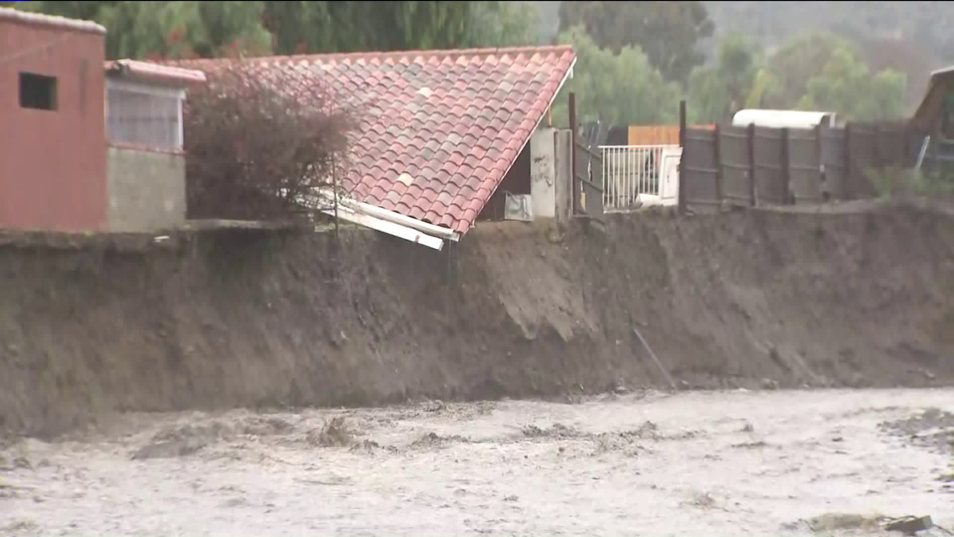 The roof of a structure appears collapsed on an eroded hillside near a rain-swollen creek in Lake Elsinore on Feb. 14, 2019. (Credit: KTLA)