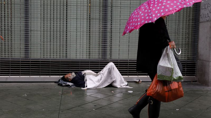 Esteban Velasquez, 54, tries to stay warm as pedestrians walk along South Broadway in downtown Los Angeles on a rainy day in January. (Credit: Francine Orr / Los Angeles Times)