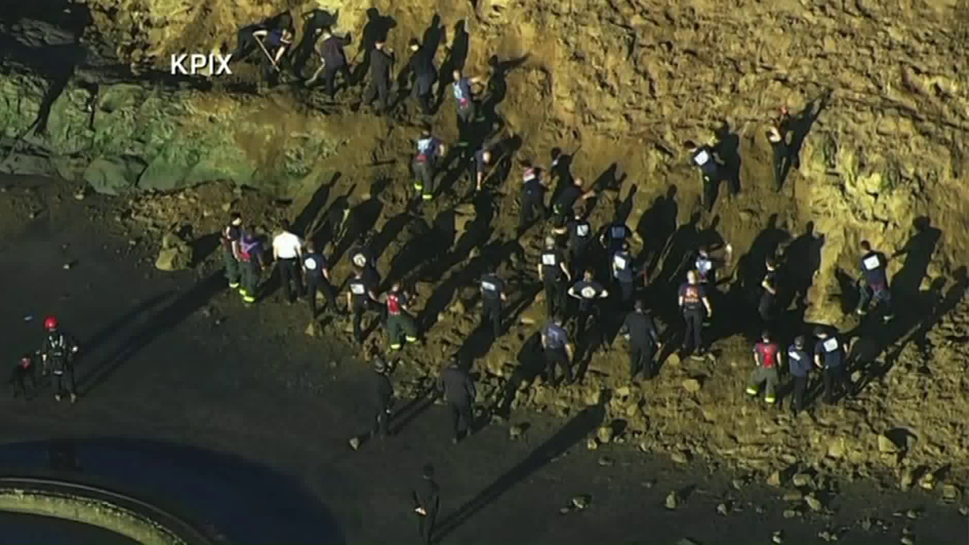Rescue workers search for the body of a woman believed to be buried by a landslide at Fort Funston beach in San Francisco on Feb. 22, 2019. (Credit: KPIX via CNN)