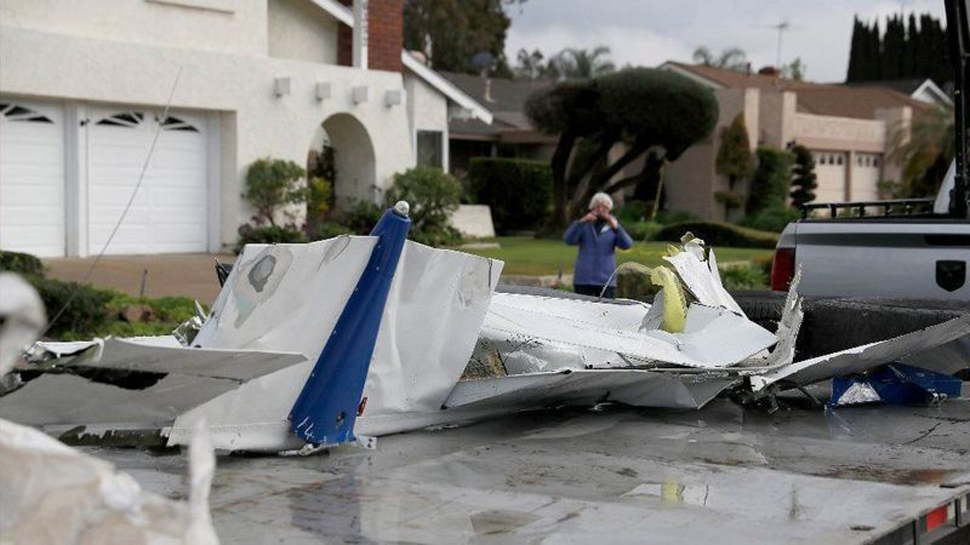 A woman takes a photo of airplane parts that landed on her property as workers remove wreckage after the crash of a Cessna airplane in Yorba Linda on Sunday, killing the pilot and four people inside a home. (Credit: Allen J. Schaben / Los Angeles Times)