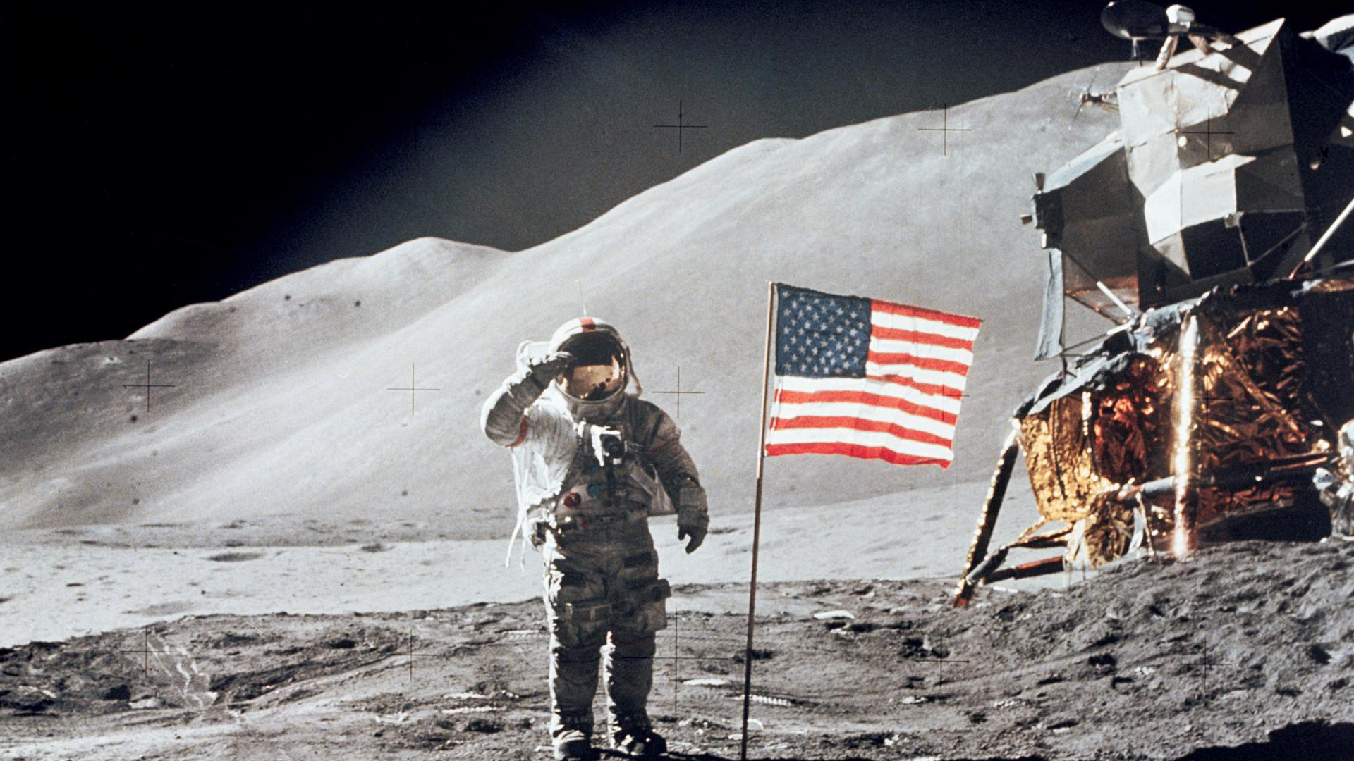 Astronaut David R. Scott, commander, gives a military salute while standing beside the U.S. flag during the Apollo 15 lunar surface extravehicular activity at the Hadley-Apennine landing site. (Credit: NASA)