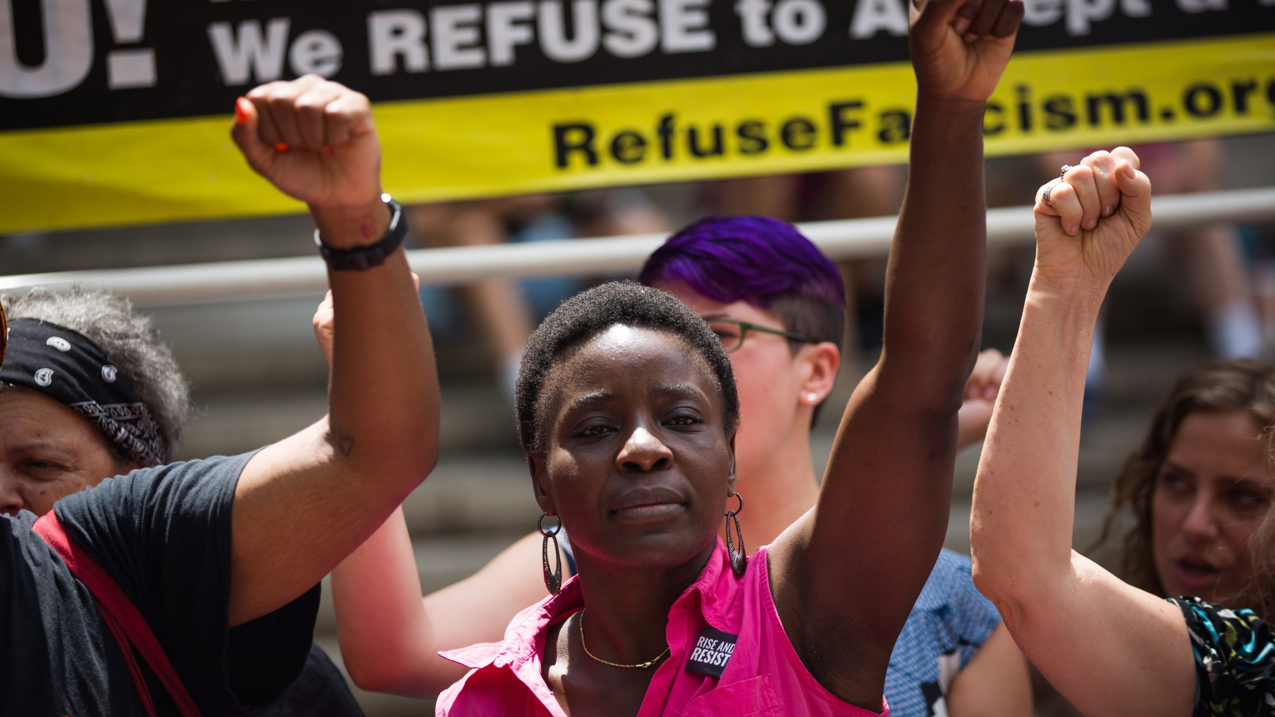Therese Okoumou, center, protests the Trump administration's immigration policies outside of the Department of Homeland Security's Cybersecurity Summit on July 31, 2018, in New York City. (Credit: Kevin Hagen/Getty Images)
