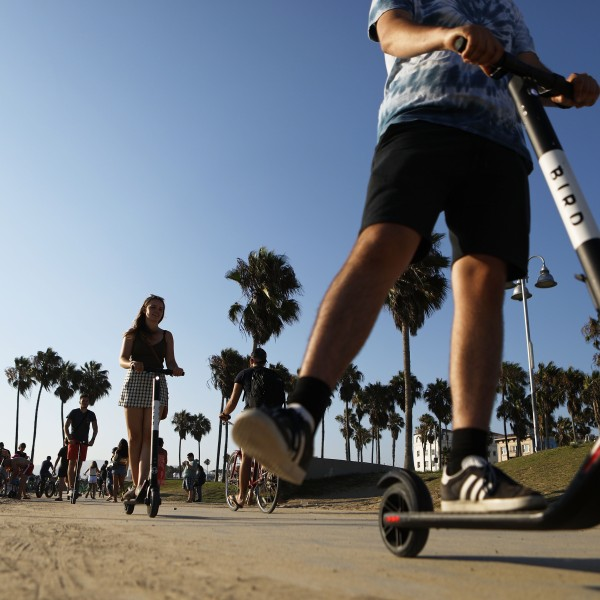 People ride Bird dockless electric scooters along Venice Beach on Aug. 13, 2018. (Credit: Mario Tama / Getty Images)