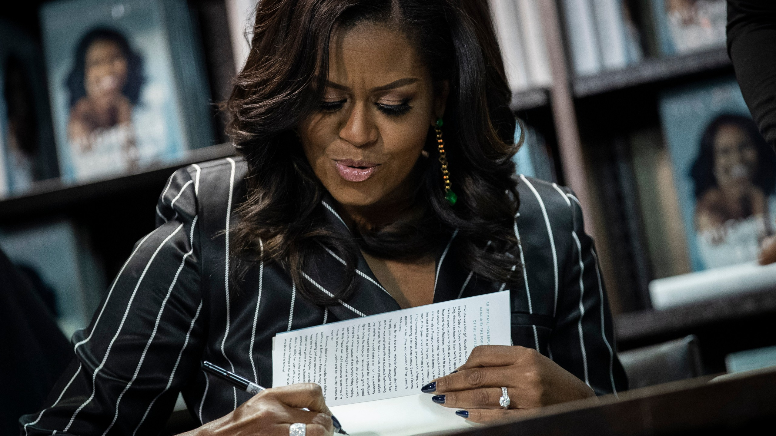 """Former First Lady Michelle Obama signs copies of her book """"Becoming"""" during a book signing event at a Barnes & Noble bookstore on Nov. 30, 2018, in New York City. (Credit: Drew Angerer/Getty Images)"""