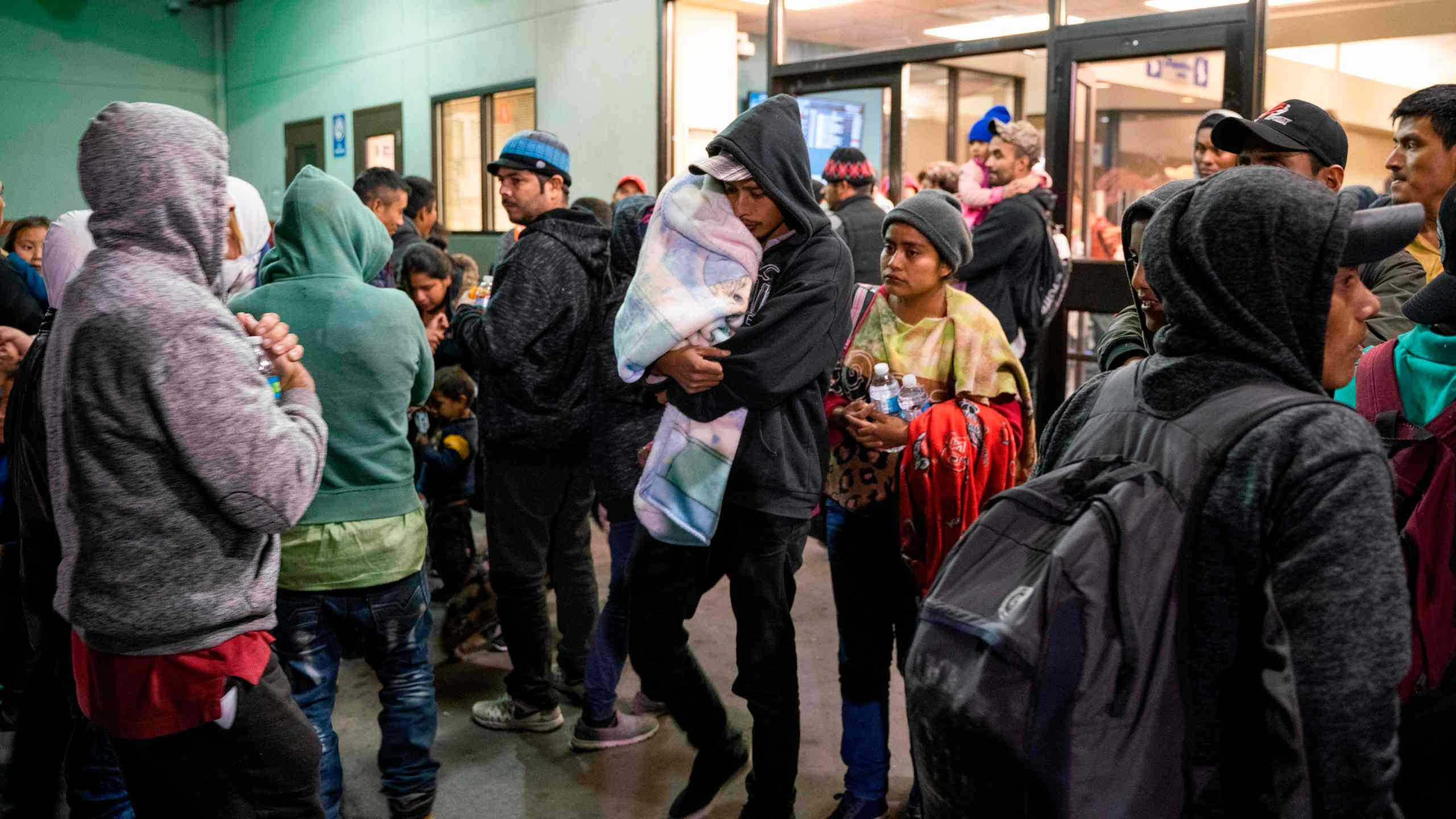 Asylum seekers stand at a bus stop after being dropped off by Immigration and Customs Enforcement at the Greyhound bus station in downtown El Paso, Texas late on Dec. 23, 2018. (Credit: PAUL RATJE/AFP/Getty Images)