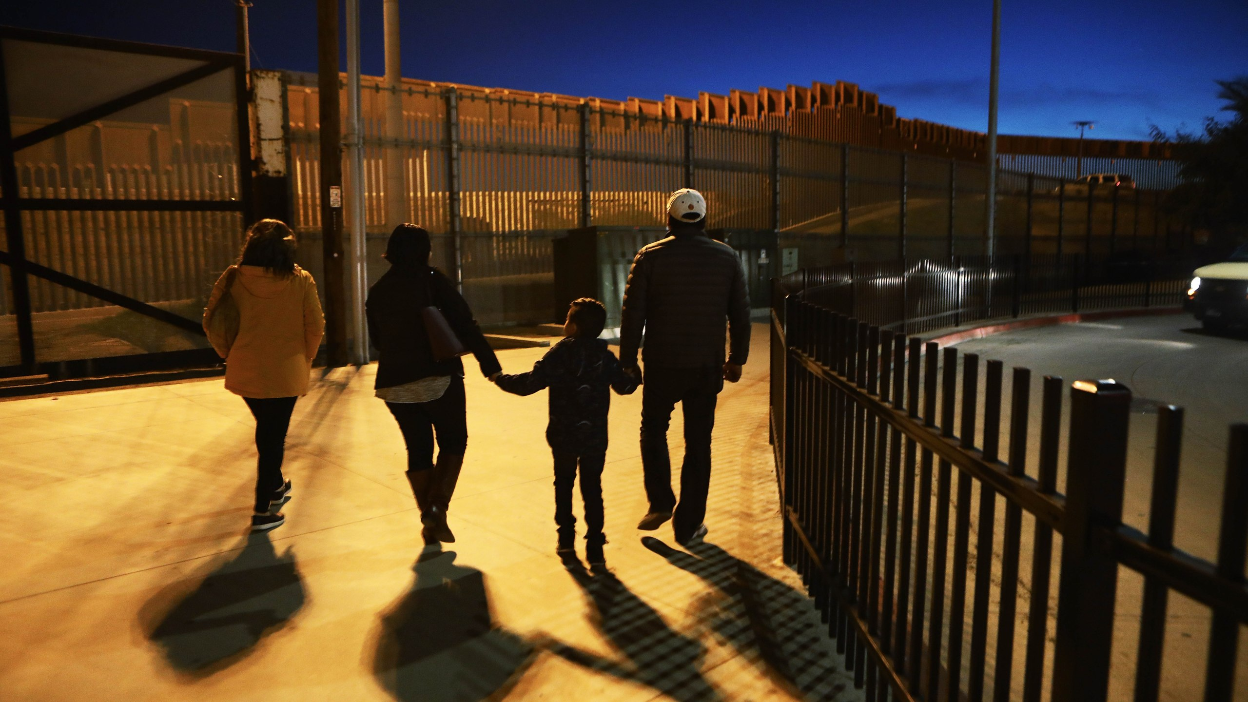 People walk on a sidewalk on the U.S. side of the U.S.-Mexico border barrier in San Diego on Jan. 25, 2019. (Credit: Mario Tama / Getty Images)