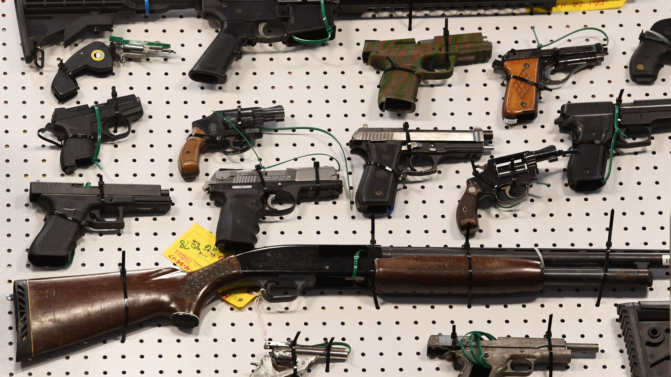 Representatives from the FBI and Los Angeles Police Department display weapons seized after a raid in which three dozen reputed members of street gangs from the San Fernando Valley and South Los Angeles were arrested on Feb. 13, 2019. (Credit: Mark Ralston / AFP / Getty Images)