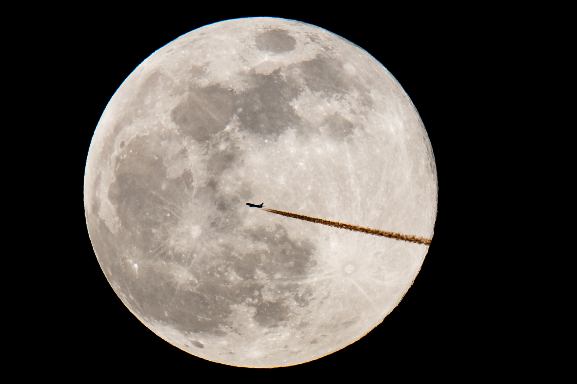 An airplane silhouettes against the Super Moon on Feb. 19, 2019, in Nuremberg, southern Germany. (Credit: DANIEL KARMANN/AFP/Getty Images)