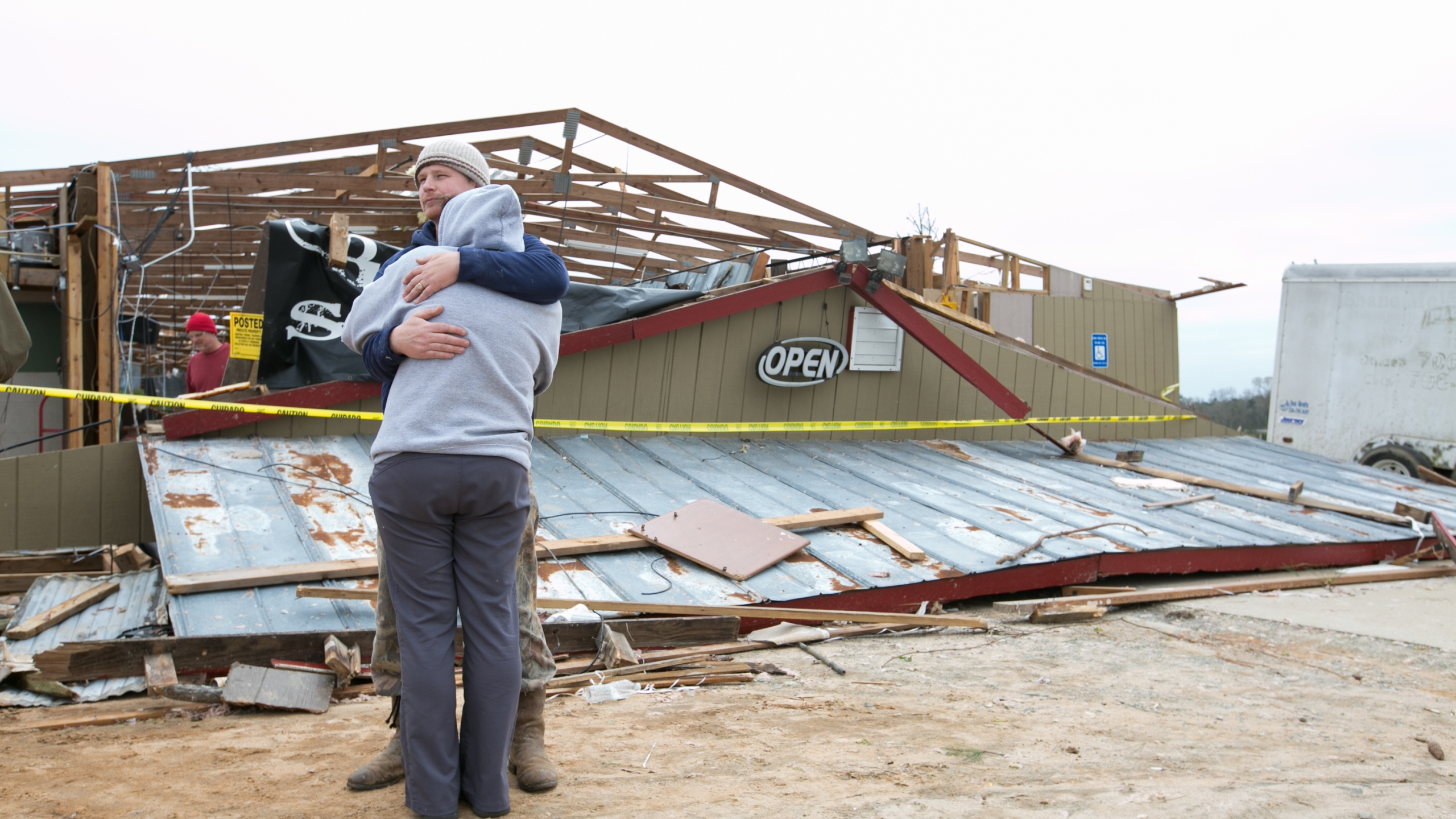 Gabe and Brandi O'Neal embrace outside of the Buck Wild Saloon on March 4, 2019, after it was destroyed by a tornado in Smith Station, Alabama. (Credit: Jessica McGowan / Getty Images)