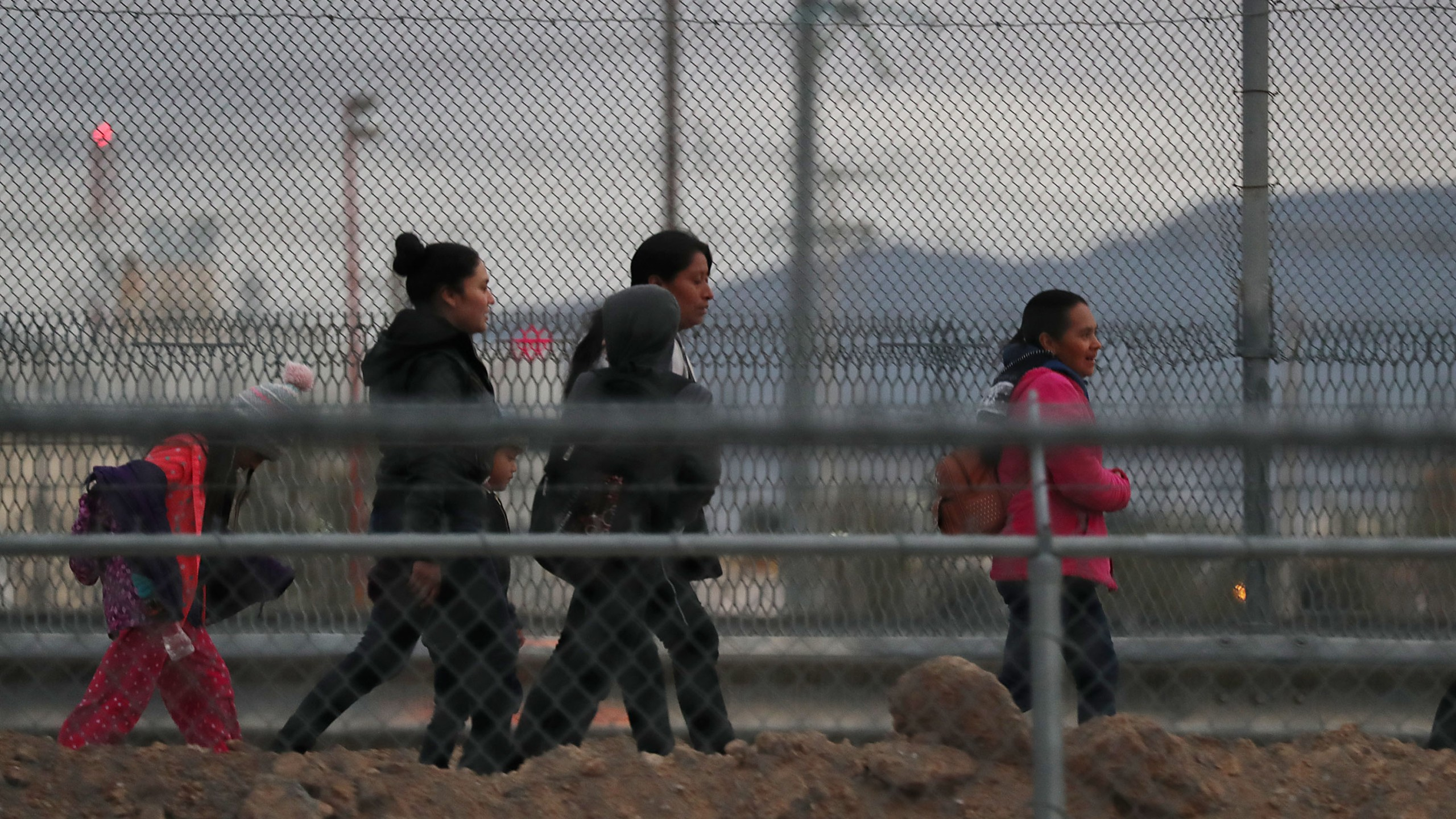 Migrants walk along the U.S.- Mexico border wall as they make their way to U.S. Border Patrol on Feb. 10, 2019 in El Paso, Texas. (Credit: Joe Raedle/Getty Images)