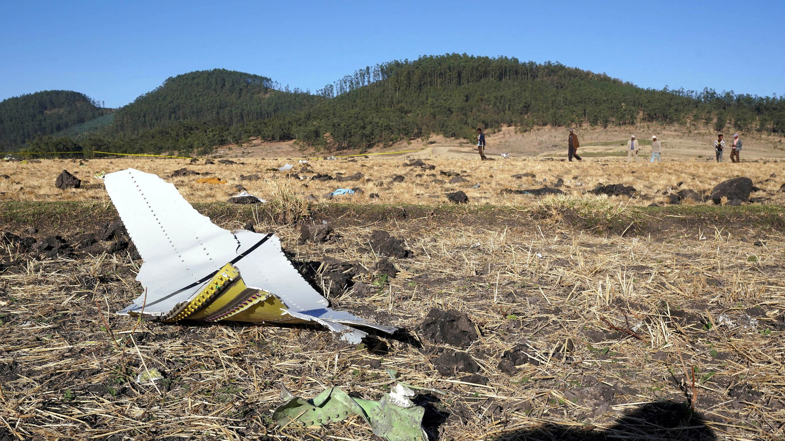 A piece of the fuselage of ET Flight 302 can be seen in the foreground as local residents collect debris at the scene where Ethiopian Airlines Flight 302 crashed in a wheat field on March 10, 2019, in Addis Ababa, Ethiopia. (Credit: Jemal Countess/Getty Images)