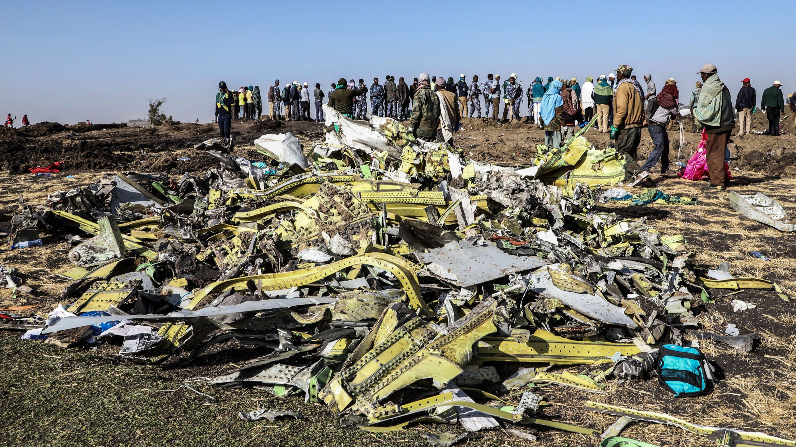 People stand near collected debris at the crash site of Ethiopia Airlines near Bishoftu, a town some 60 kilometres southeast of Addis Ababa, Ethiopia, on March 11, 2019. (Credit: MICHAEL TEWELDE/AFP/Getty Images)