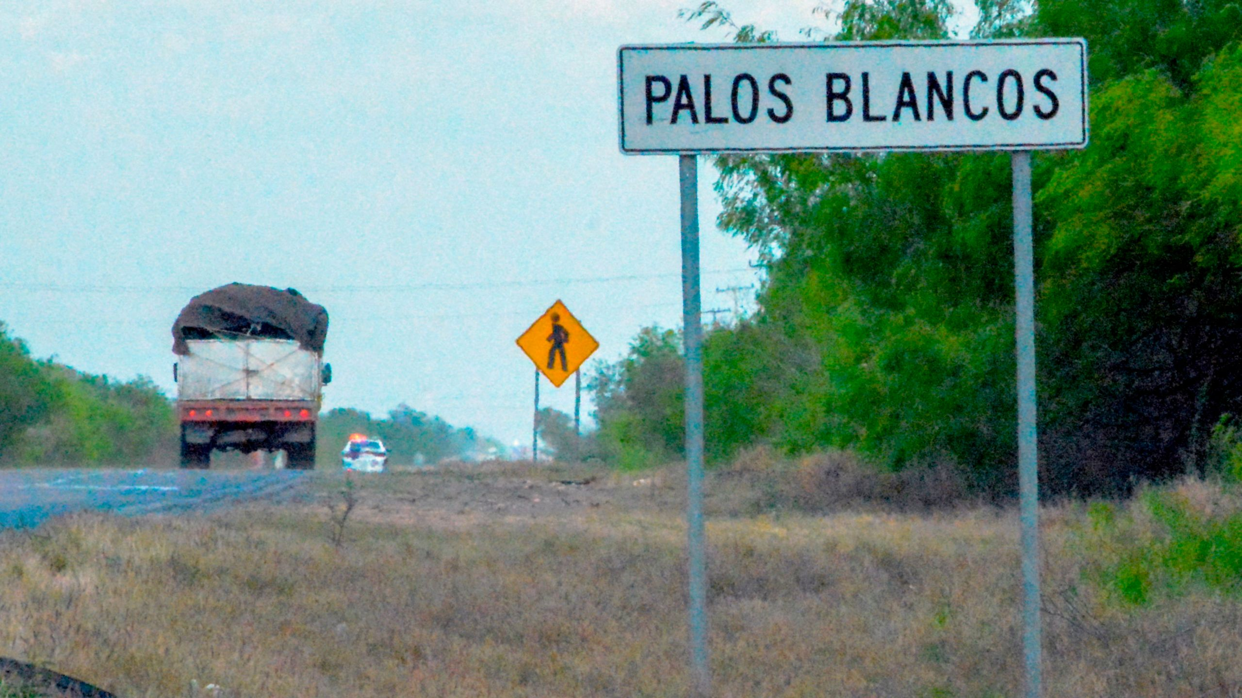 A truck drives past a sign on the Reynosa-San Fernando road in Palos Blancos in Tamaulipas state in northeasten Mexico, on March 12, 2019. (Credit: Jesus Gonzalez/AFP/Getty Images)