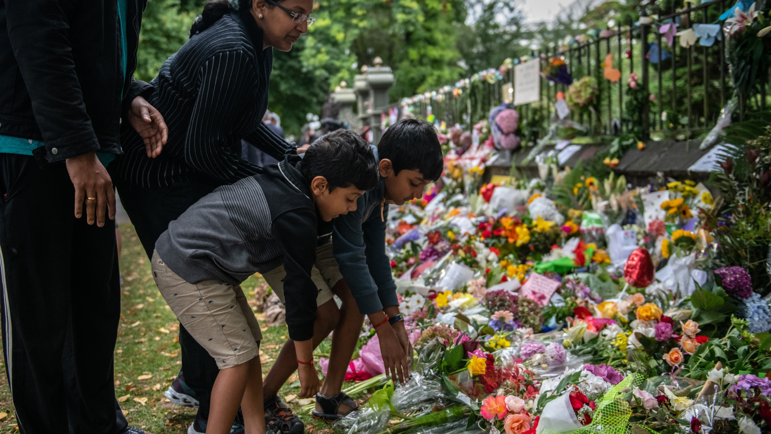 A family lays flowers by the wall of the Botanic Gardens on March 17, 2019, in Christchurch, New Zealand. (Credit: Carl Court/Getty Images)