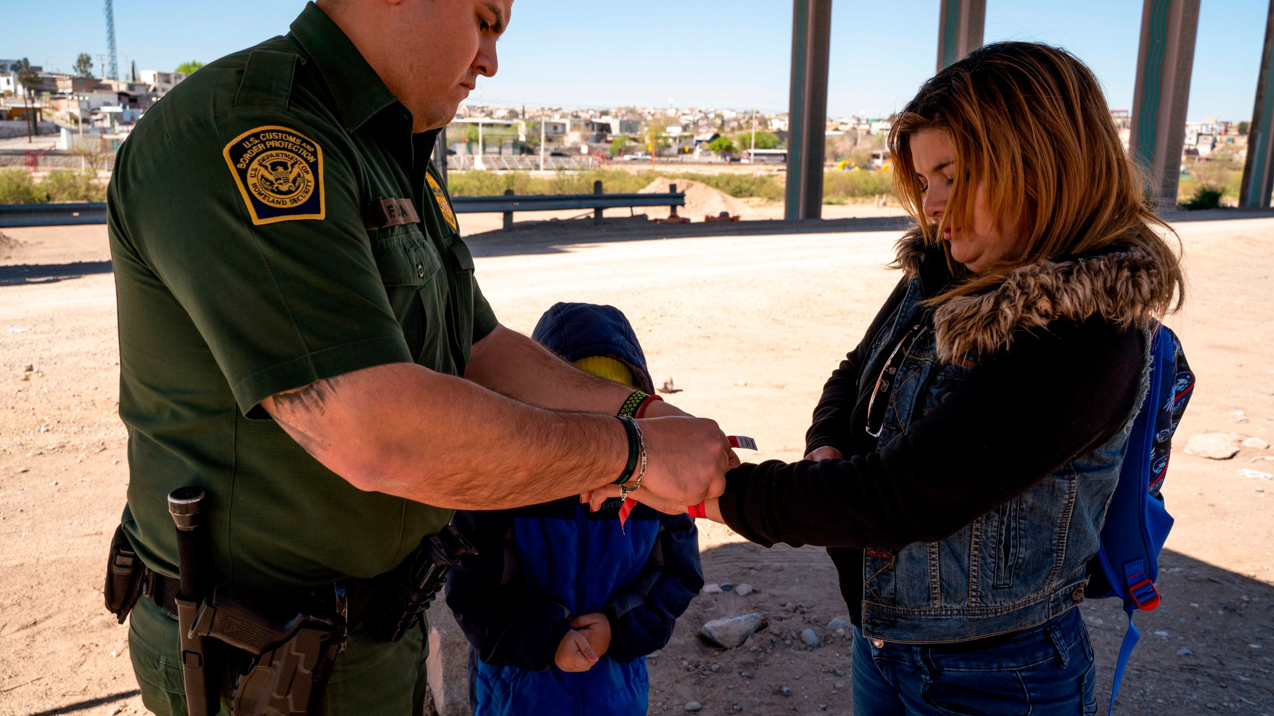 A mother and her son are given arm bands after turning themselves in to Border Patrol agents to claim asylum after crossing the Rio Grande in El Paso, Texas, on March 19, 2019. (Credit: Paul Ratje / AFP / Getty Images)