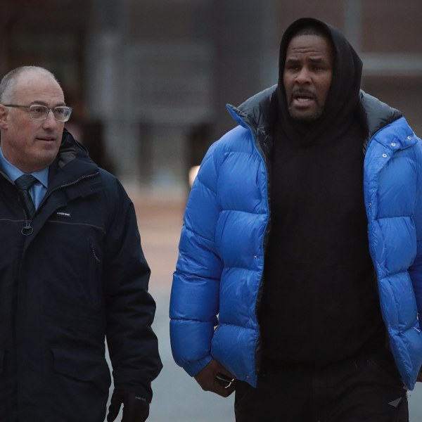 Singer R. Kelly, right, and his attorney Steve Greenberg leave Cook County jail in Chicago after Kelly posted $100,000 bond on Feb. 25, 2019. (Credit: Scott Olson / Getty Images)
