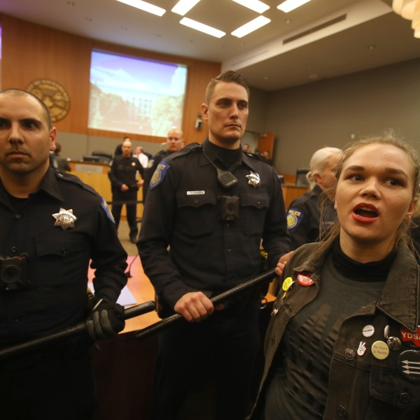 Sacramento police officers guard the dais as activists disrupt a Sacramento City Council meeting on March 5, 2019. (Credit: Justin Sullivan / Getty Images)