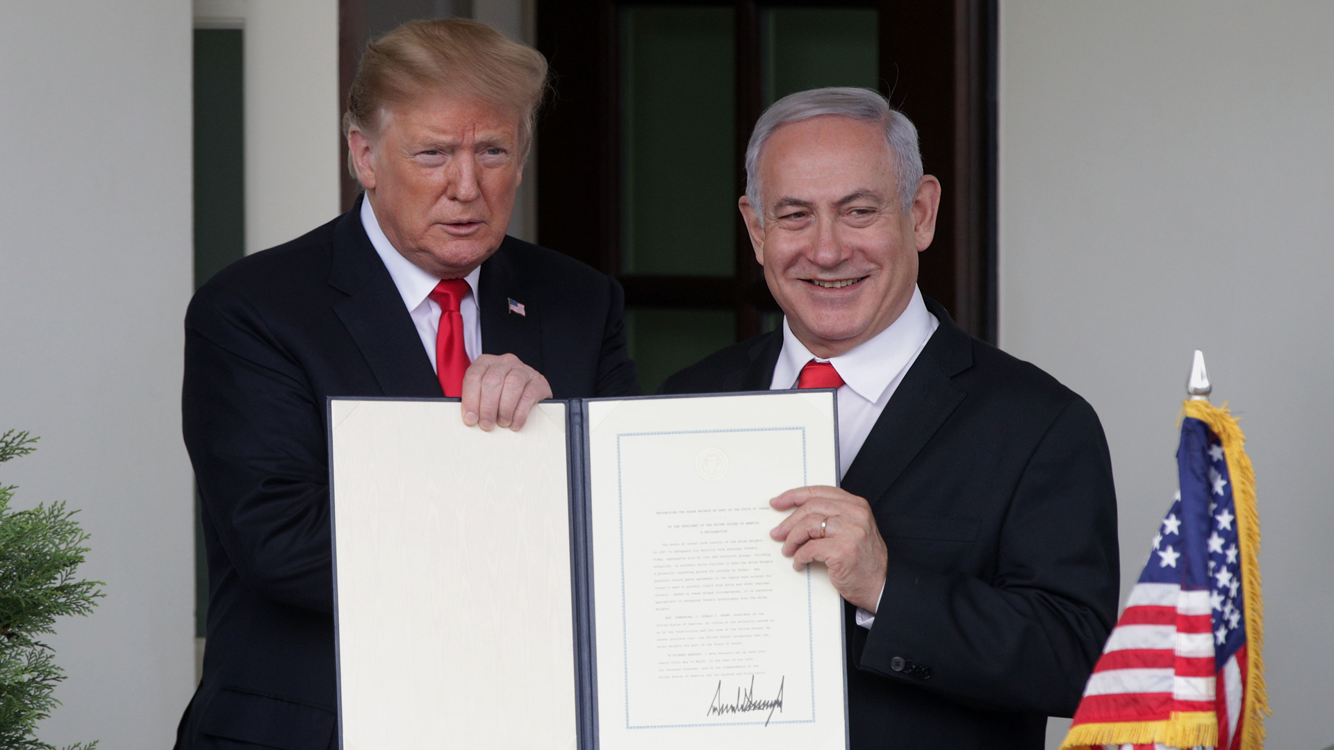 Donald Trump and Prime Minister of Israel Benjamin Netanyahu show members of the media the proclamation Trump signed recognizing Israel's sovereignty over Golan Heights at the White House on March 25, 2019. (Credit: Alex Wong/Getty Images)