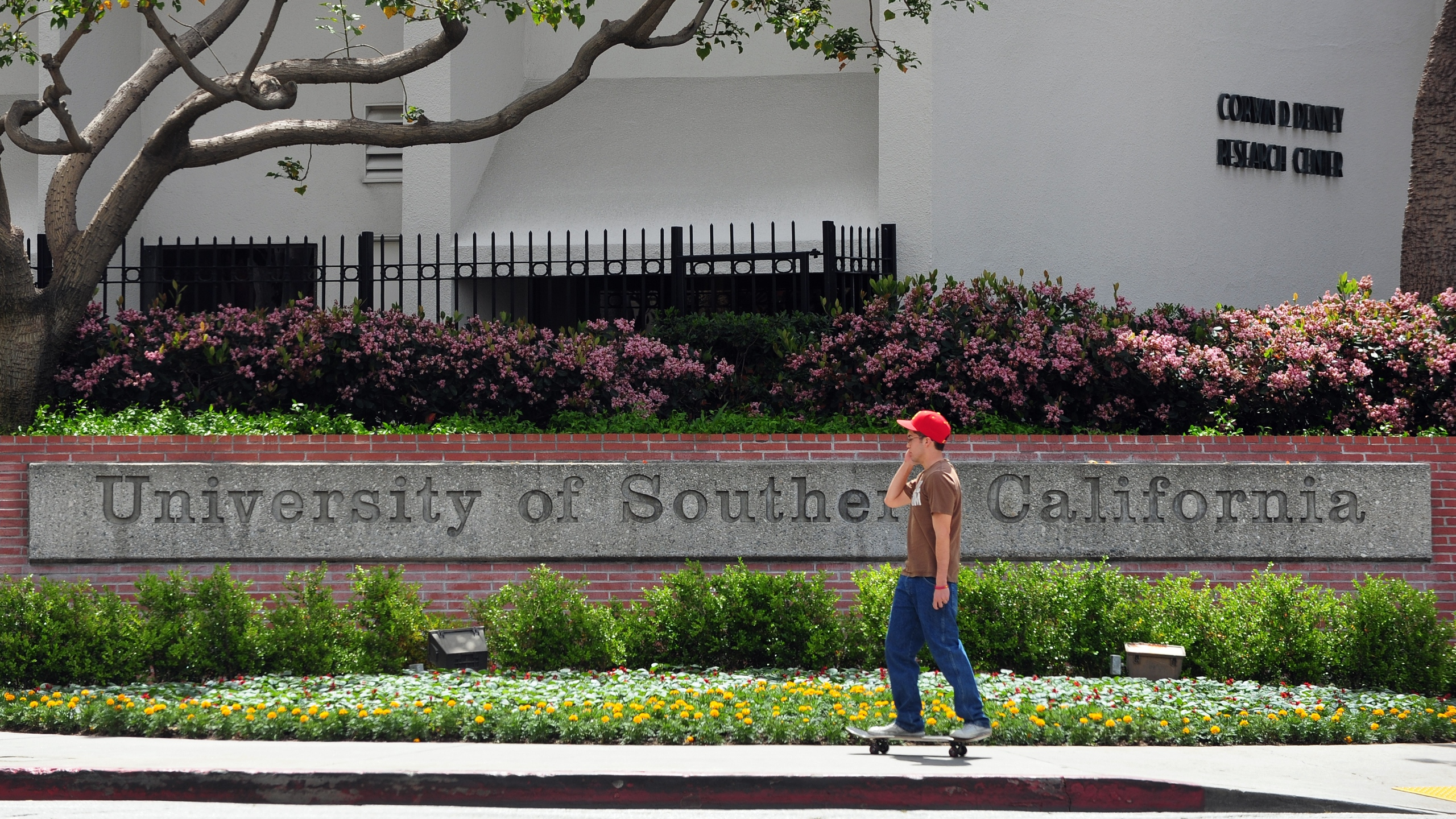 A student rides his skateboard past an entrance to the University of Southern California campus in Los Angeles on April 11, 2012. (Credit: FREDERIC J. BROWN/AFP/Getty Images)