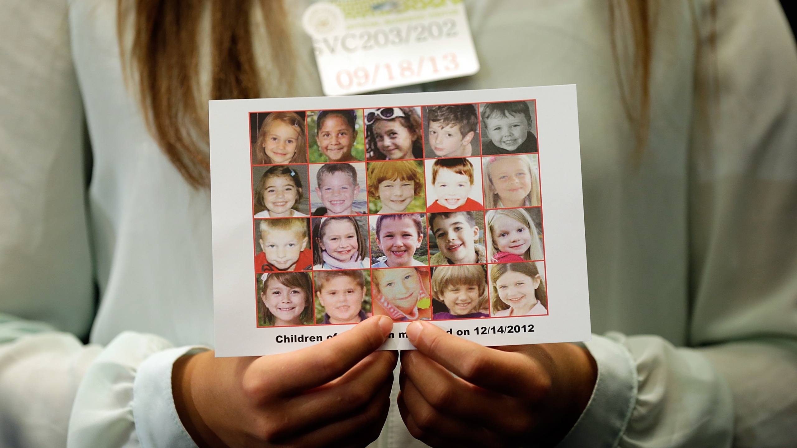 Kyra Murray holds a photo of the victims of the shooting at Sandy Hook Elementary School during a press conference at the U.S. Capitol on Sept. 18, 2013 in Washington, D.C. (Credit: Win McNamee/Getty Images)