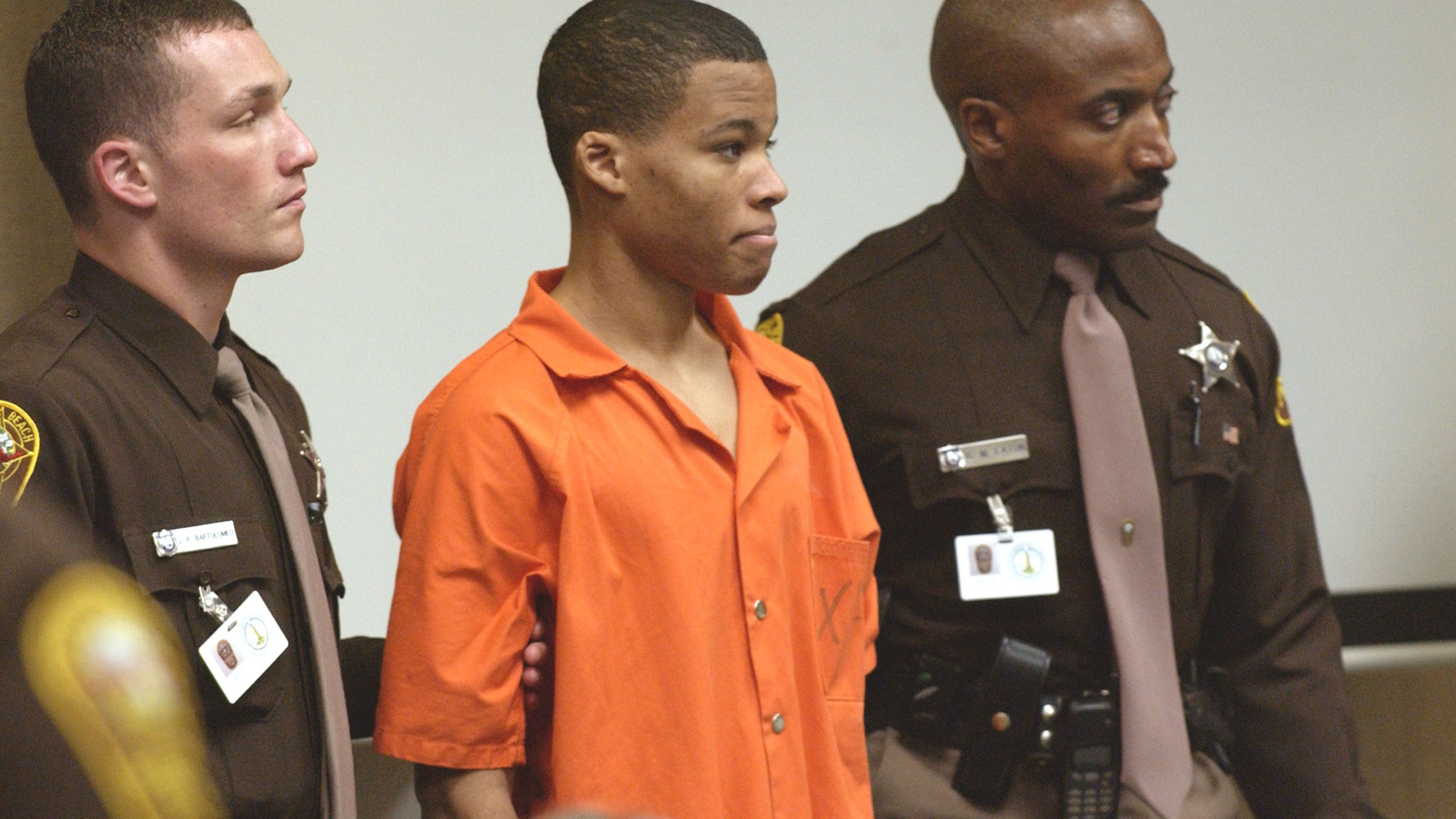 Sniper suspect Lee Boyd Malvo (C) is escorted by deputies as he is brought into court to be identified by a witness during the murder trial in courtroom 10 at the Virginia Beach Circuit Court October 22, 2003 in Virginia Beach, Virginia. (Credit: Davis Turner-Pool/Getty Images)