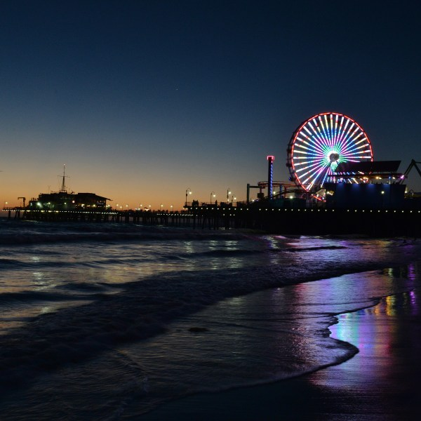 The sun sets over the Pacific Amusement Park at Santa Monica pier on Oct. 19, 2014. (Credit: Mark Ralston/AFP/Getty Images)