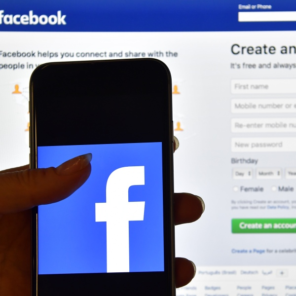 A person holds an iPhone displaying the Facebook app logo in front of a computer screen showing the Facebook login page on August 3, 2016 in London, England. (Credit: Carl Court/Getty Images)