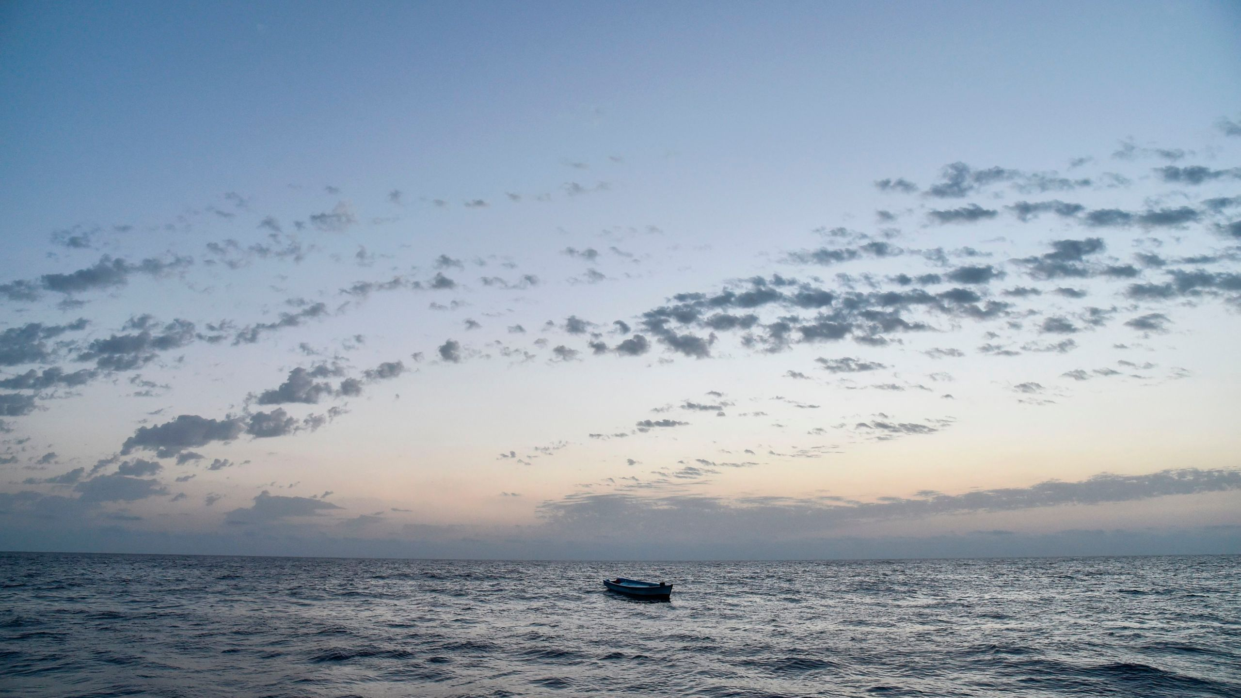 A small wooden boat used by migrants to cross the Mediterranean Sea is abandoned after a rescue operation on November 3, 2016, off the Libyan coast. (Credit: ANDREAS SOLARO/AFP/Getty Images)