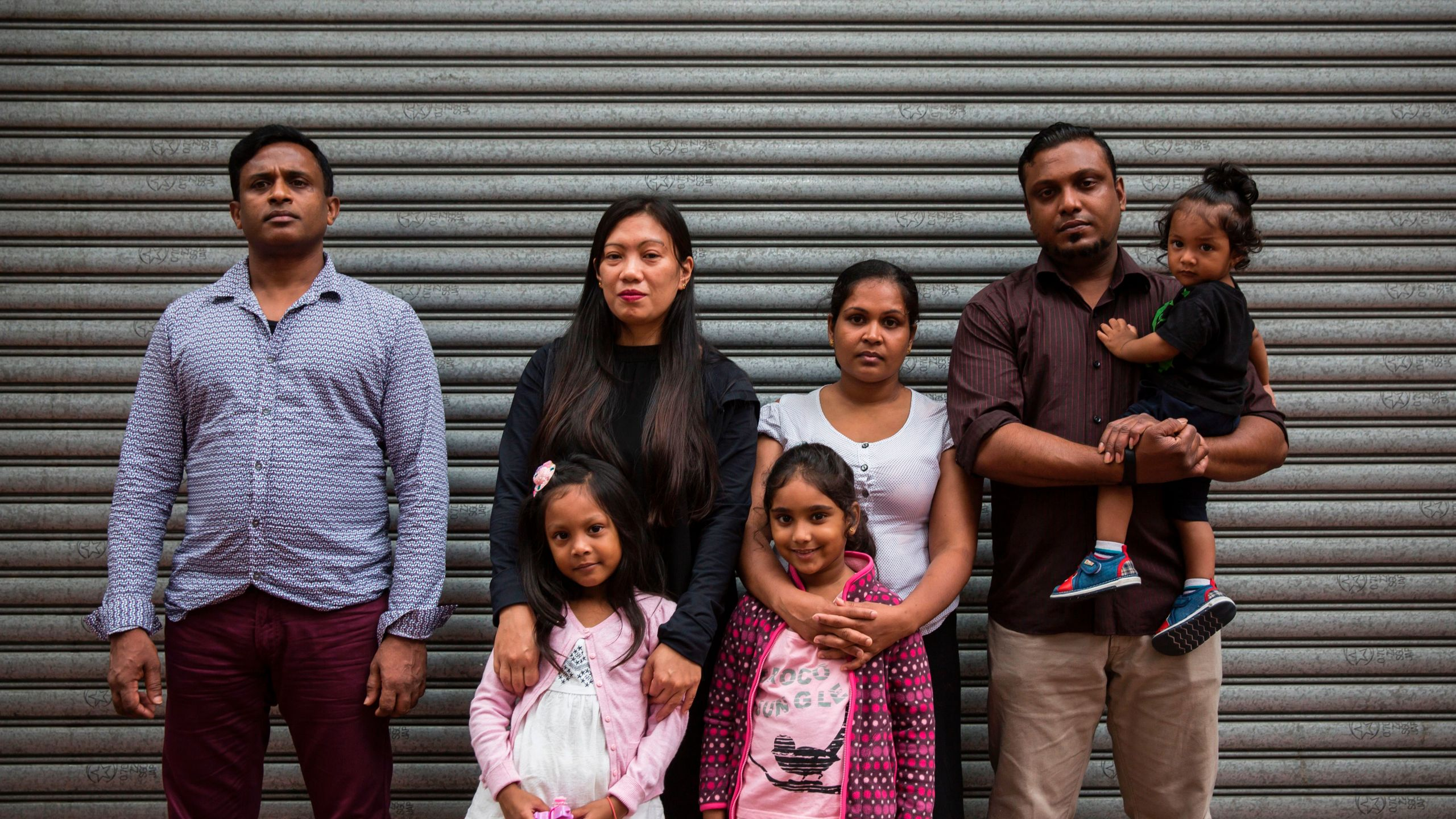 Sri Lankan refugee Ajith Puspa (left), Filipino refugee Vanessa Rodel (second from left) with her daughter Keana, Sri Lankan refugees Nadeeka Nonis (third from right) with her partner Supun Thilina Kellapatha (second from right) and children Sethumdi (fourth from right) and Dinath (right) pose for a photo in front of the Torture Claims Appeal Board building in Hong Kong on July 17, 2017, before attending an appeal hearing over the rejection of their refugee status in the southern Chinese city. (Credit: ISAAC LAWRENCE/AFP/Getty Images)