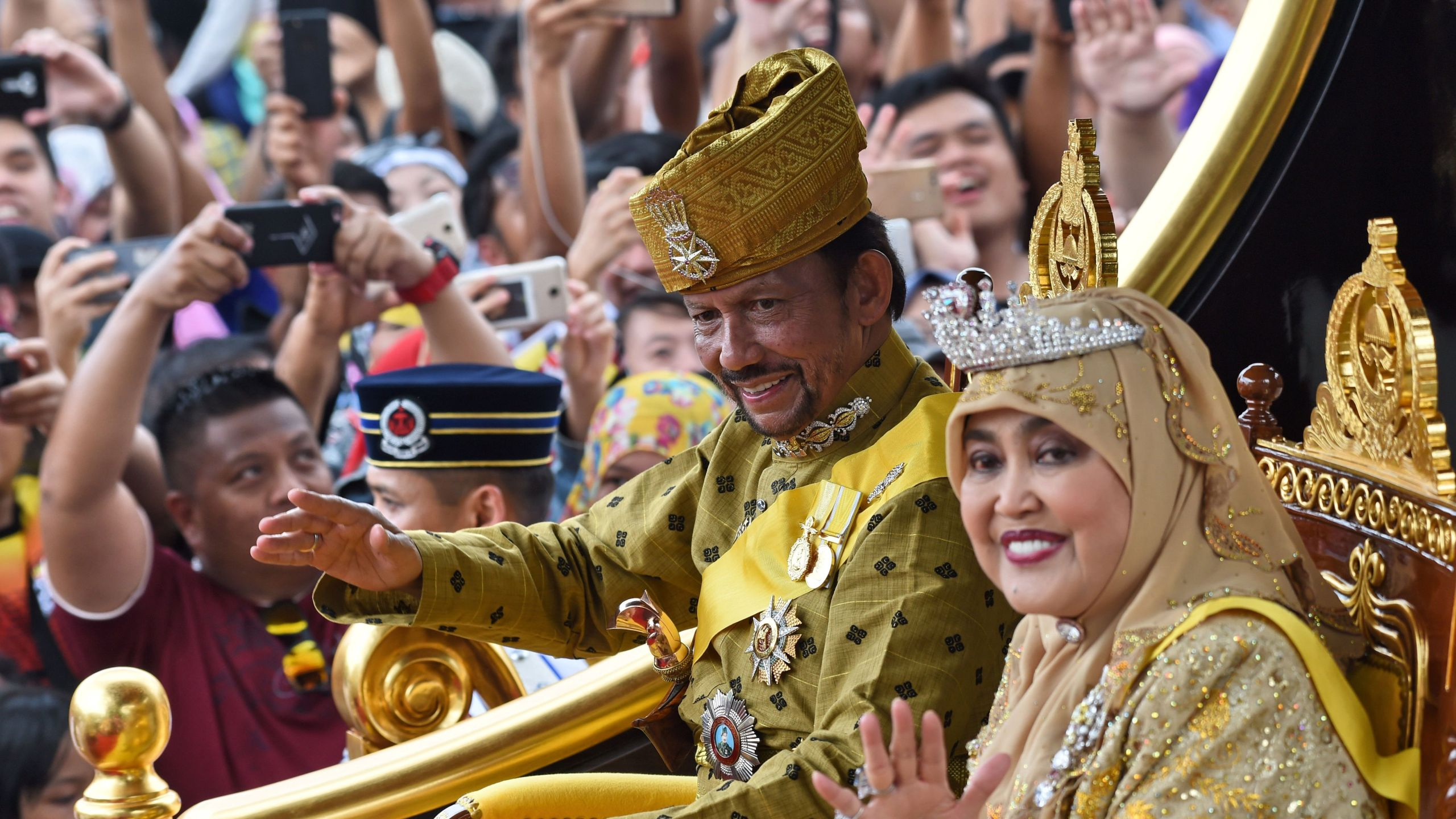 Brunei's Sultan Hassanal Bolkiah and Queen Saleha ride in a royal chariot during a procession to mark his golden jubilee of accession to the throne in Bandar Seri Begawan on October 5, 2017. (Credit: Roslan Rahman/AFP/Getty Images)