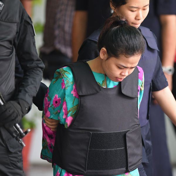 Indonesian defendant Siti Aisyah is escorted by police personnel following her appearance at the Malaysian Chemistry Department in Petaling Jaya, outside Kuala Lumpur on October 9, 2017. (Credit: Mohd Rasfan/AFP/Getty Images)