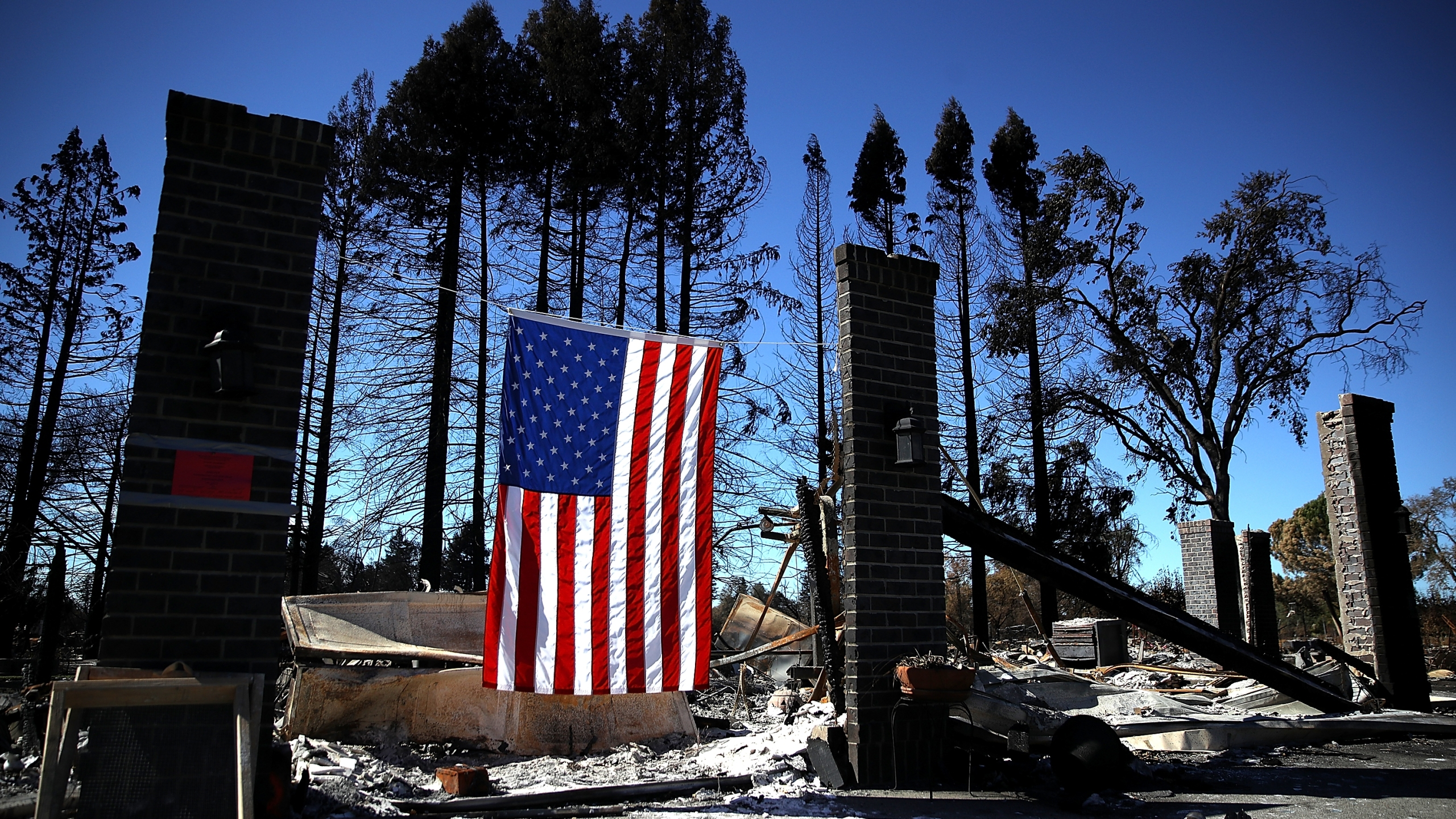 An American flag hangs in front of a home in the Coffey Park neighborhood that was destroyed by the Tubbs Fire on Oct. 23, 2017, in Santa Rosa. (Credit: Justin Sullivan/Getty Images)