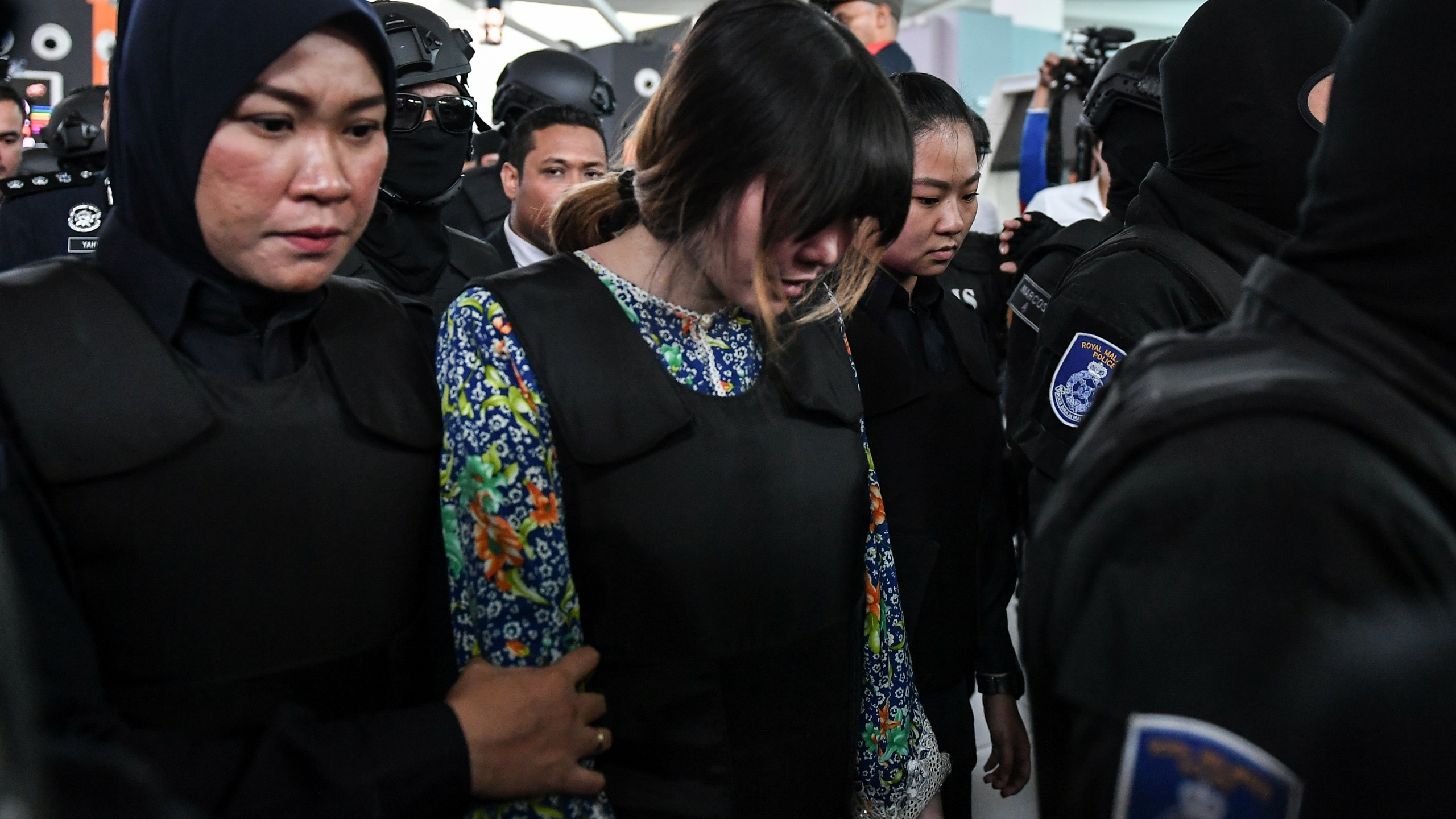 Vietnamese defendant Doan Thi Huong (C) is escorted by police personnel towards the low-cost carrier Kuala Lumpur International Airport 2 (KLIA2) in Sepang during a visit to the scene of the murder as part of the Shah Alam High Court trial process on October 24, 2017, for her alleged role in the assassination of Kim Jong-Nam. (Credit: Mohd Rasfan/AFP/Getty Images)