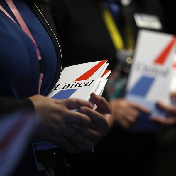 United Airlines flight attendants pass out retro ticket jackets to passengers boarding flight 747 for its final trip from San Francisco International Airport to Honolulu, Hawaii, on Nov. 7, 2017. (Credit: Justin Sullivan / Getty Images)