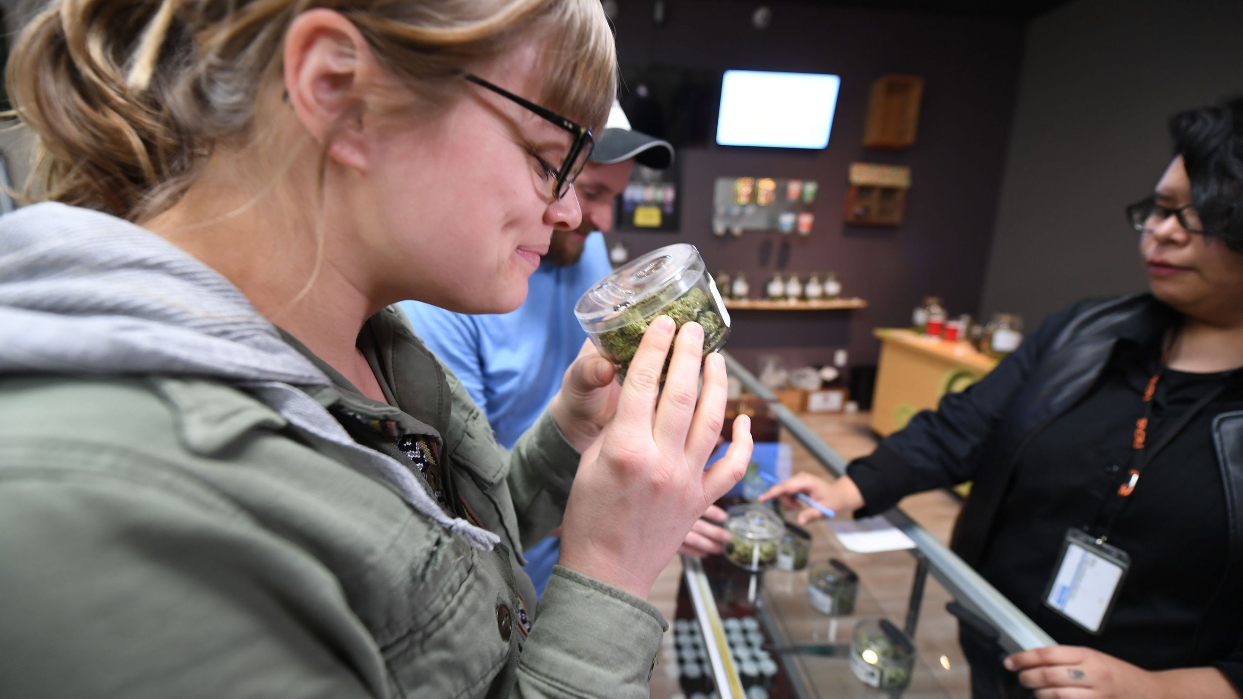 Tourist Laura Torgerson, visiting from Arizona, smells cannabis buds at the Green Pearl Organics dispensary in Desert Hot Springs on the first day of legal recreational marijuana sales in California, Jan. 1, 2018. (Credit: Robyn Beck / AFP / Getty Images)