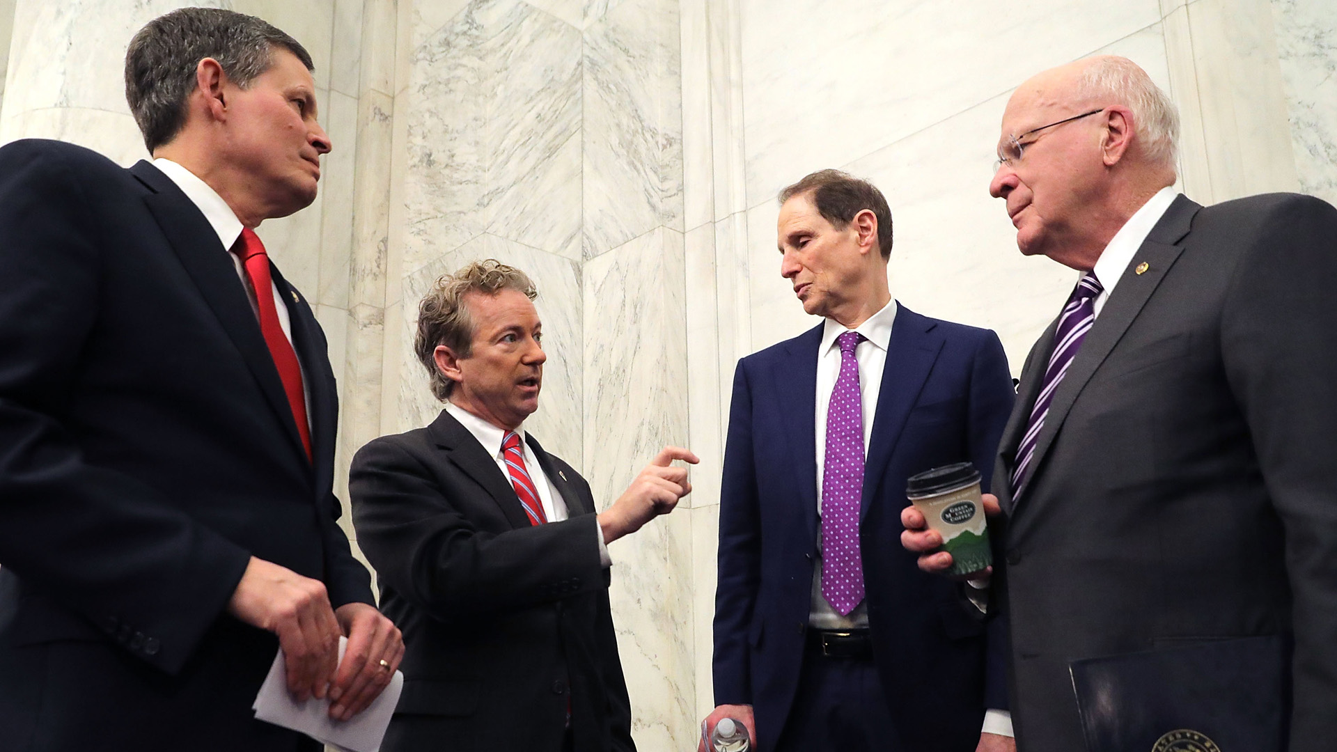 (L-R) Sen. Steve Daines (R-MT), Sen. Rand Paul (R-KY), Sen. Ron Wyden (D-OR) and Sen. Patrick Leahy (D-VT) talk strategy before a news conference about their proposed reforms to the Foreign Intelligence Surveillance Act in the Russell Senate Office Building on Capitol Hill January 16, 2018 in Washington, DC. (Credit: Chip Somodevilla/Getty Images)