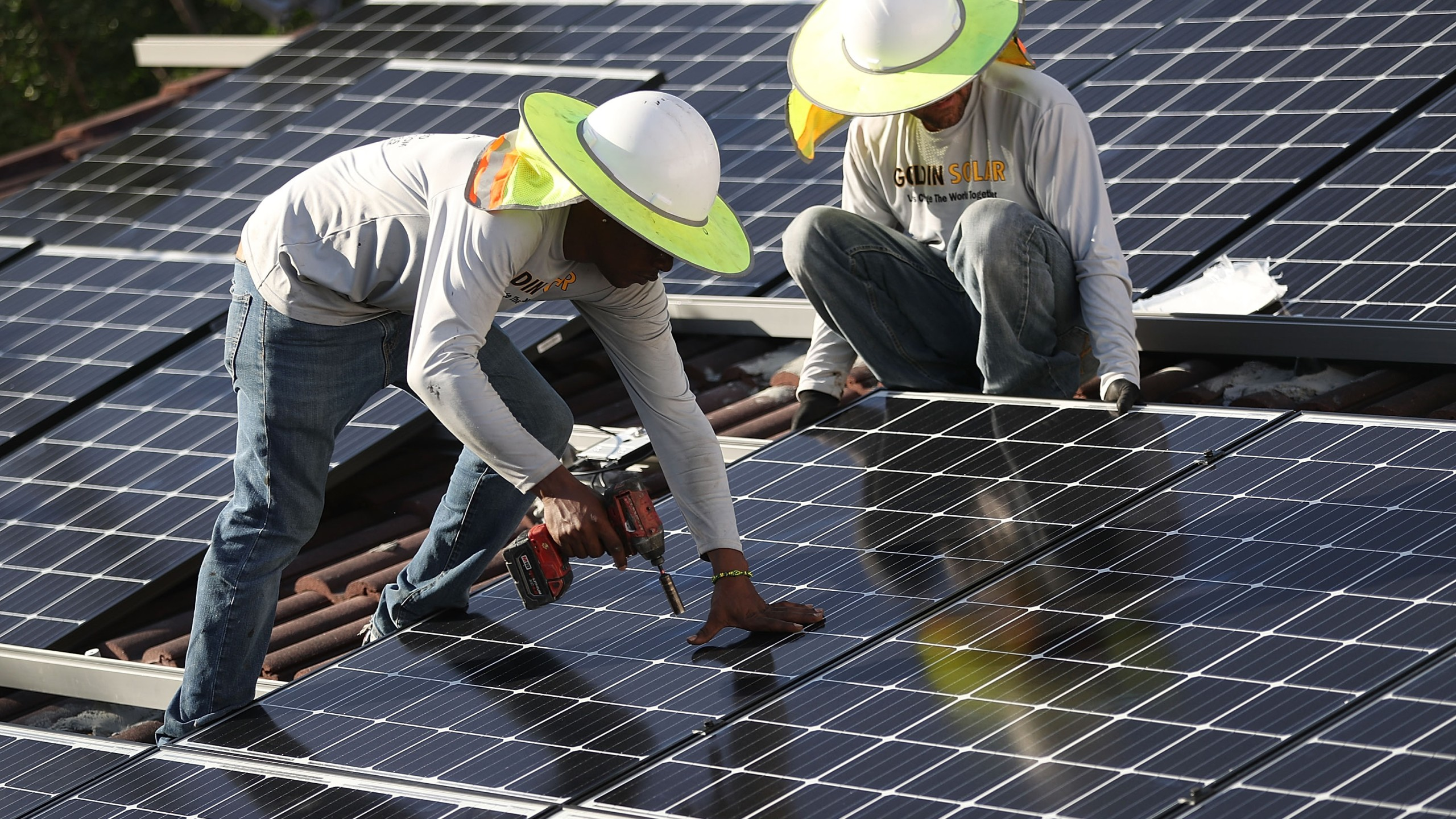 Workers from the Goldin Solar company install a solar panel system on the roof of a home in Palmetto Bay, Florida. (Credit: Joe Raedle/Getty Images)
