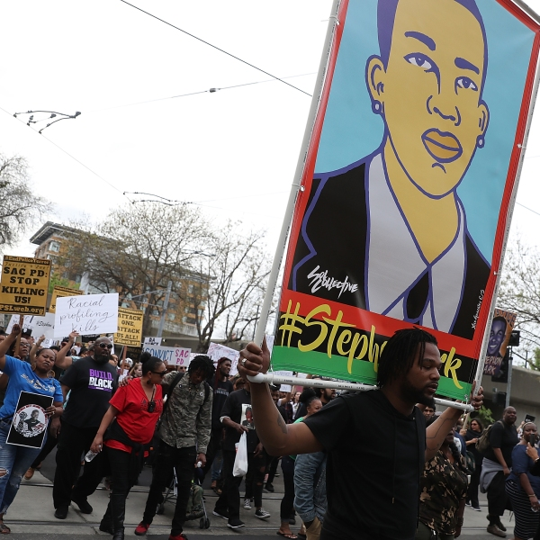 Black Lives Matter protesters hold an illustration of Stephon Clark as they march on April 4, 2018 in Sacramento. (Credit: Justin Sullivan/Getty Images)