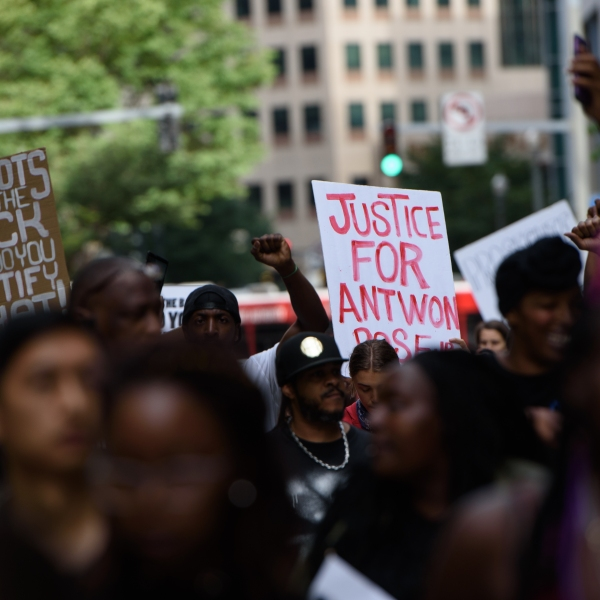 """A demonstrator holds up a sign that reads """"Justice for Antwon Rose"""" during a protest a day after the funeral for Rose on June 26, 2018 in downtown Pittsburgh, Pennsylvania.(Credit: Justin Merriman/Getty Images)"""