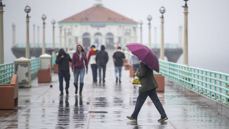 People use umbrellas and bundle up with rain jackets while walking down the pier amid light rain showers in Manhattan Beach on Feb. 28. (Credit: Allen J. Schaben / Los Angeles Times)