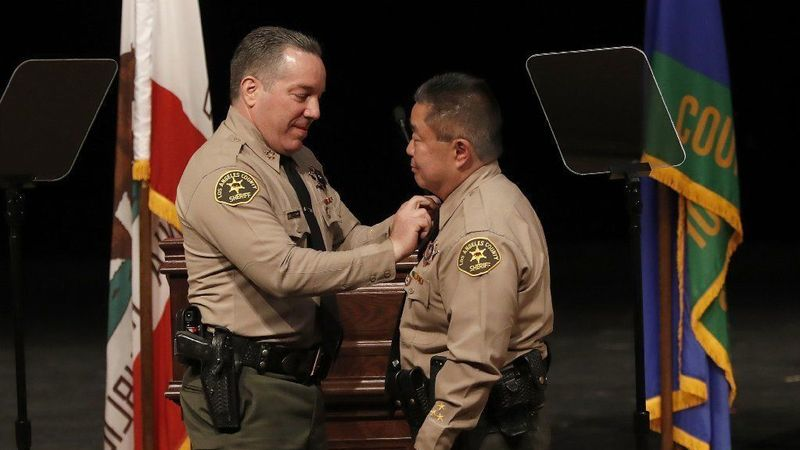 Los Angeles County Sheriff Alex Villanueva, left, places a pin on the collar of Assistant Sheriff Tim Murakami during a ceremony at East Los Angeles College on Dec. 3, 2018. (Credit: Mel Melcon / Los Angeles Times)