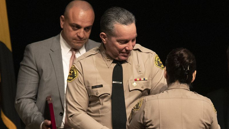 Los Angeles County Sheriff's Deputy Caren Mandoyan, left, looks on as newly elected L.A. Sheriff Alex Villanueva prepares to have his new badge pinned on him by his wife during a ceremony Dec. 3, 2018. (Credit: Mel Melcon / Los Angeles Times)