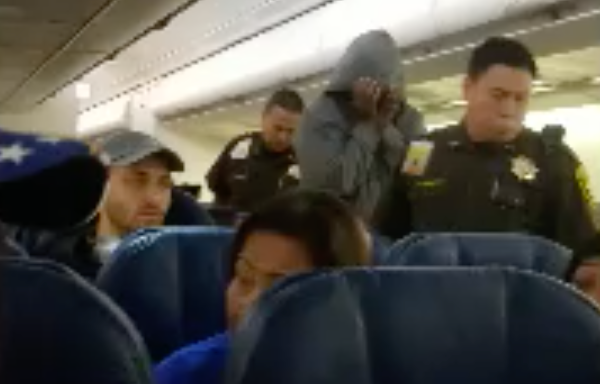 Officials escort a Hawaiian Airlines passenger off the plane in Honolulu on March 19, 2019. (Credit: Derek Smiling)
